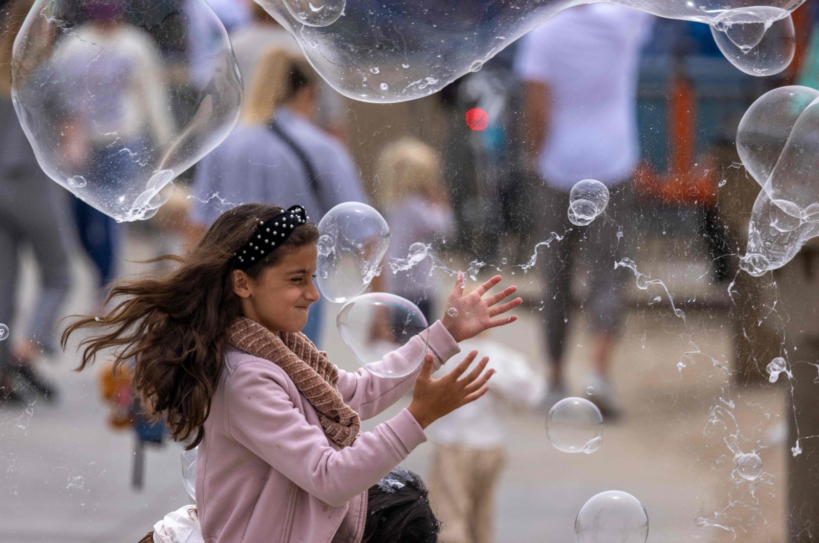Children chase bubbles near the Santa Monica Pier as crowds gather on Memorial Day as shutdowns are relaxed in Santa Monica, California, May 31, 2021. (AFP Photo)