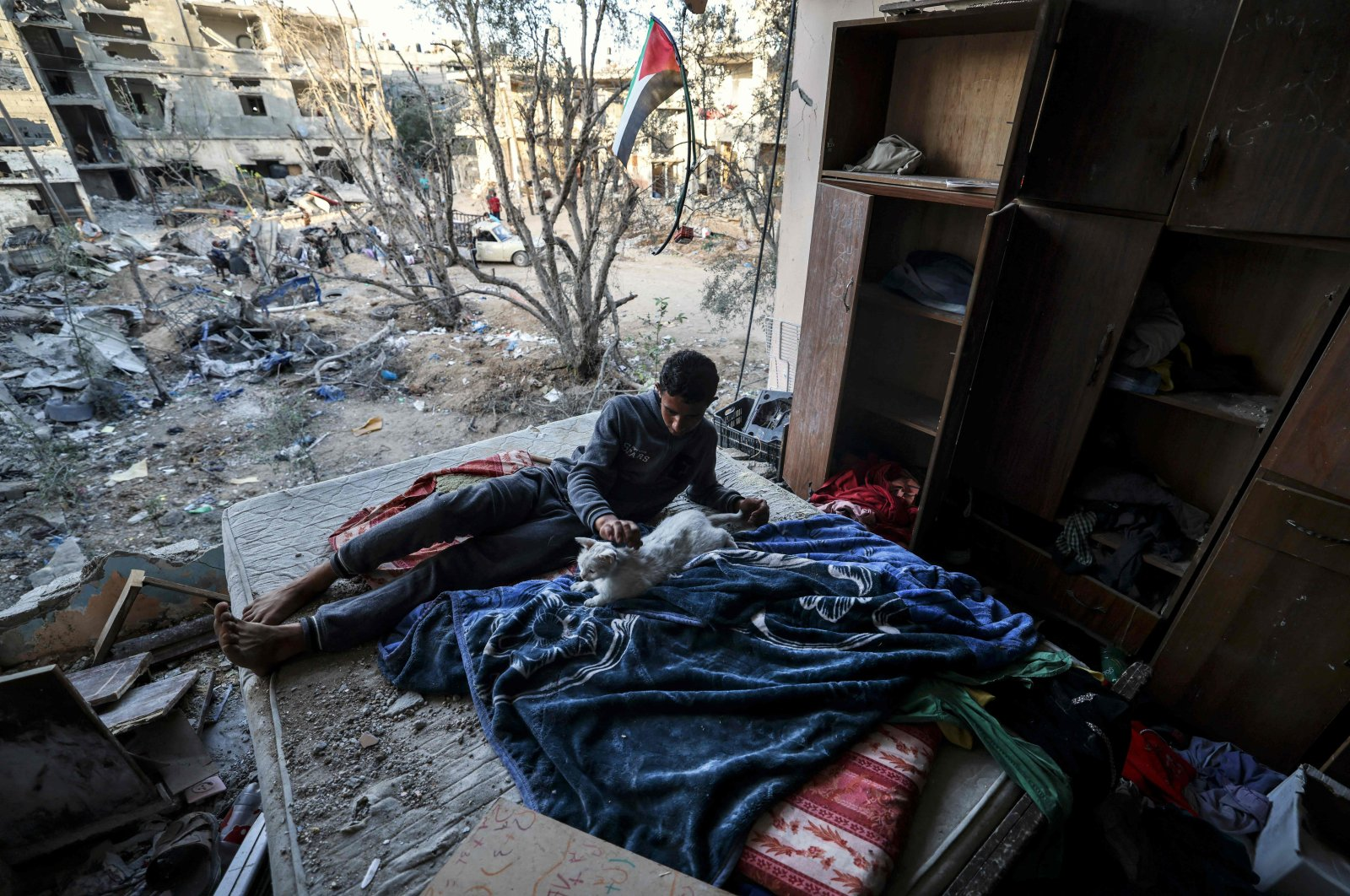 A young Palestinian pets a cat in a building heavily damaged during recent Israeli strikes more than a week after a cease-fire brought an end to 11 days of hostilities between Israel and Gaza rulers Hamas, Beit Hanun, northern Gaza Strip, June 1, 2021. (AFP Photo)