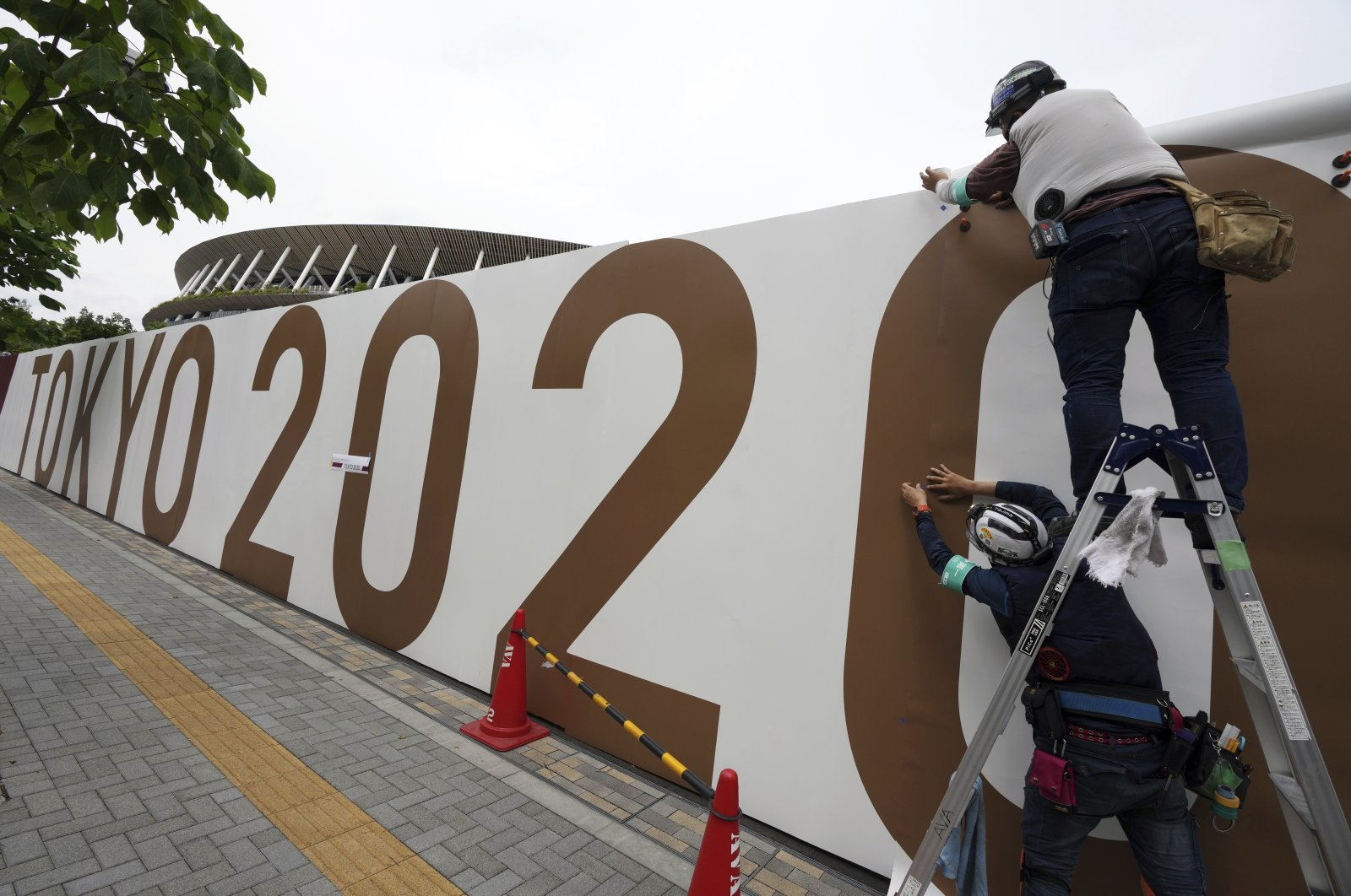 Workers paste the overlay on the wall of the National Stadium, where the opening ceremony and many other events are scheduled for the Tokyo 2020 Olympics, Tokyo, Japan, June 2, 2021. (AP Photo)