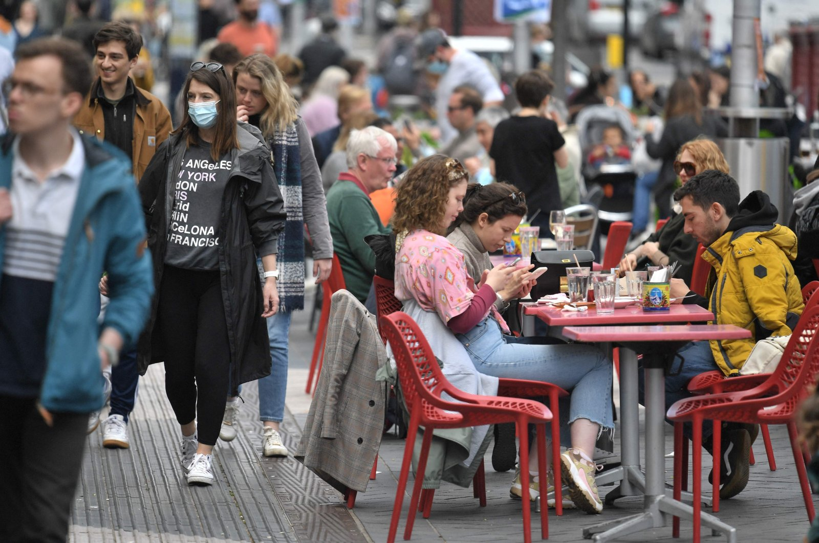 Members of the public enjoy refreshments at tables set up outside a cafe in south Kensington, London, U.K., May 18, 2021. (AFP Photo)