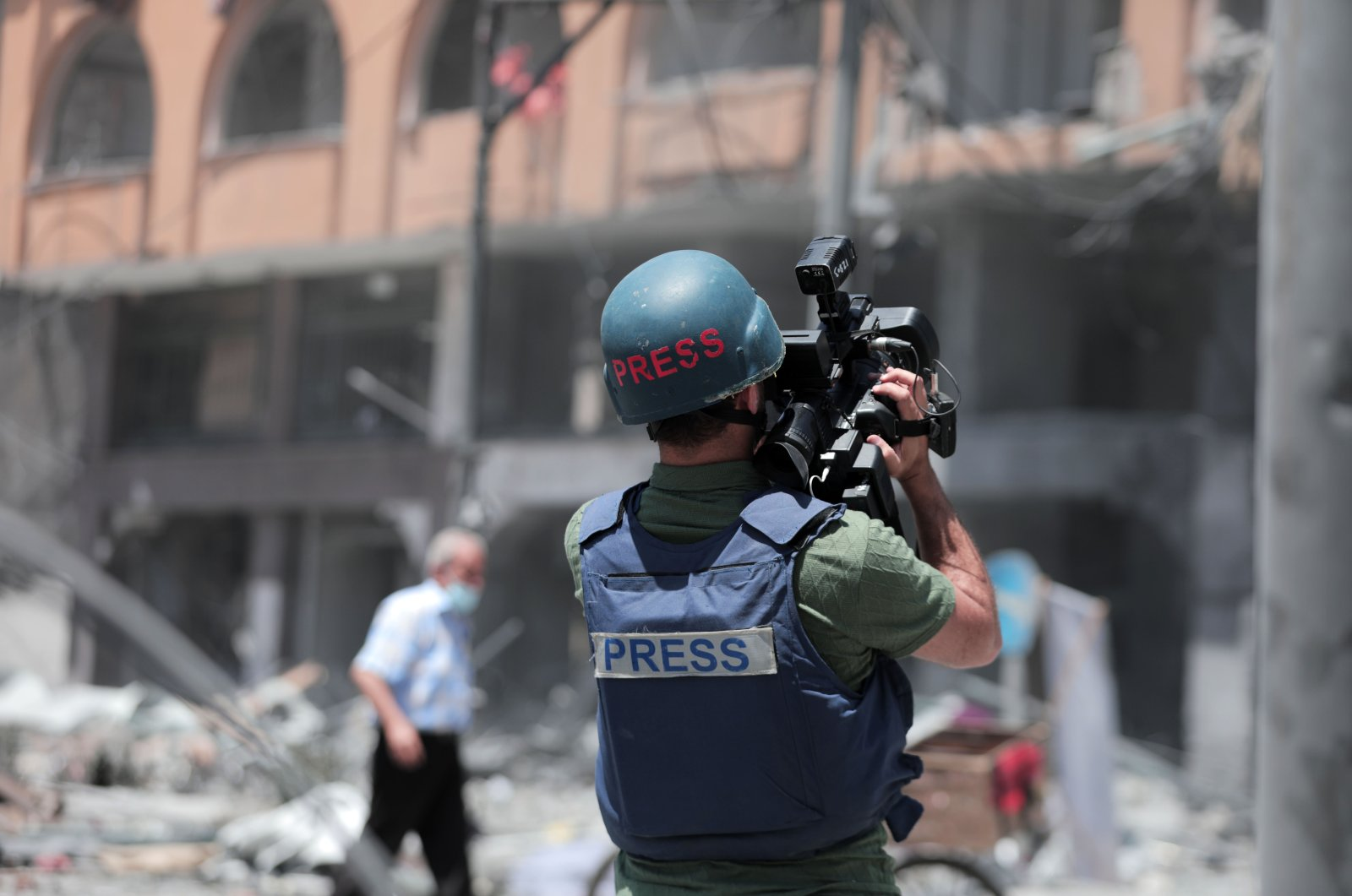 A Palestinian journalist films the aftermath of the Israeli attacks in Gaza City, Palestine, May 12, 2021. (Photo by Getty Images)