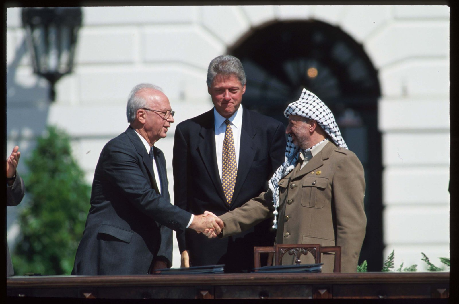 Palestine Liberation Organization (PLO) Chairperson Yasir Arafat (R) and Israeli Prime Minister Yitzhak Rabin (L) shake hands after the signing of the Oslo Accords in front of U.S. President Bill Clinton, Washington, D.C., U.S., Sept. 13, 1993. (Photo by Getty Images)
