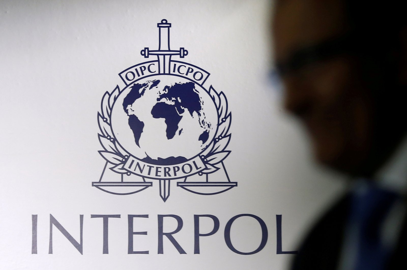 A man passes an Interpol logo during the handing over ceremony of the new premises for Interpol's Global Complex for Innovation, a research and development facility, in Singapore, September 30, 2014. (REUTERS Photo)