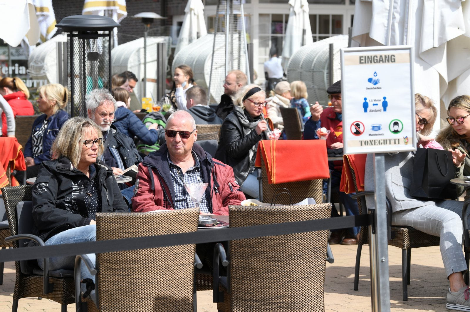 People sit in a cafe amid the coronavirus pandemic at the Baltic Sea resort Timmendorfer Strand, Germany, May 8, 2021. (Reuters Photo)