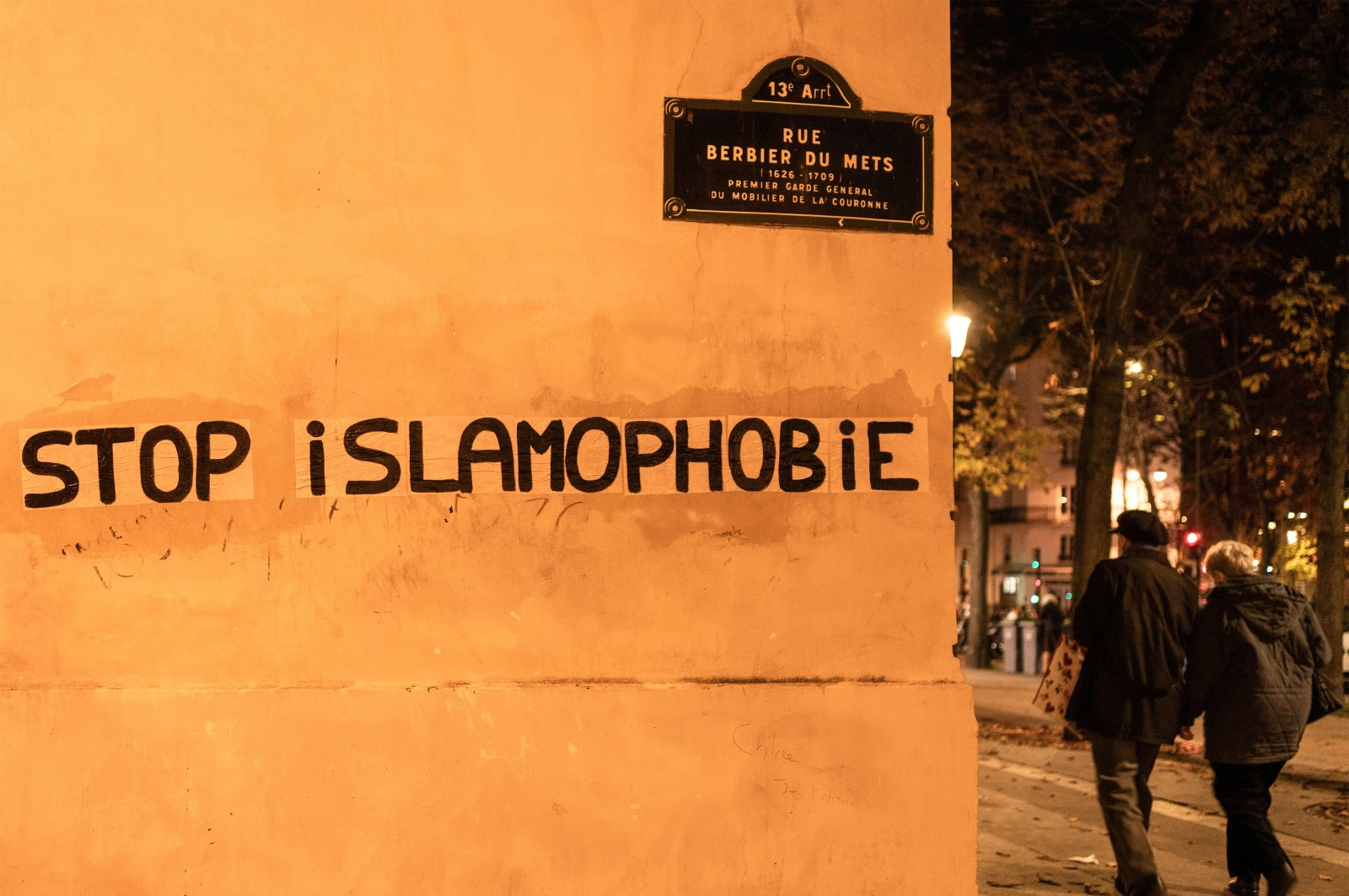 """People walk past a graffito that reads """"Stop Islamophobia"""" in Paris, France, Oct. 26, 2020. (Getty Images)"""