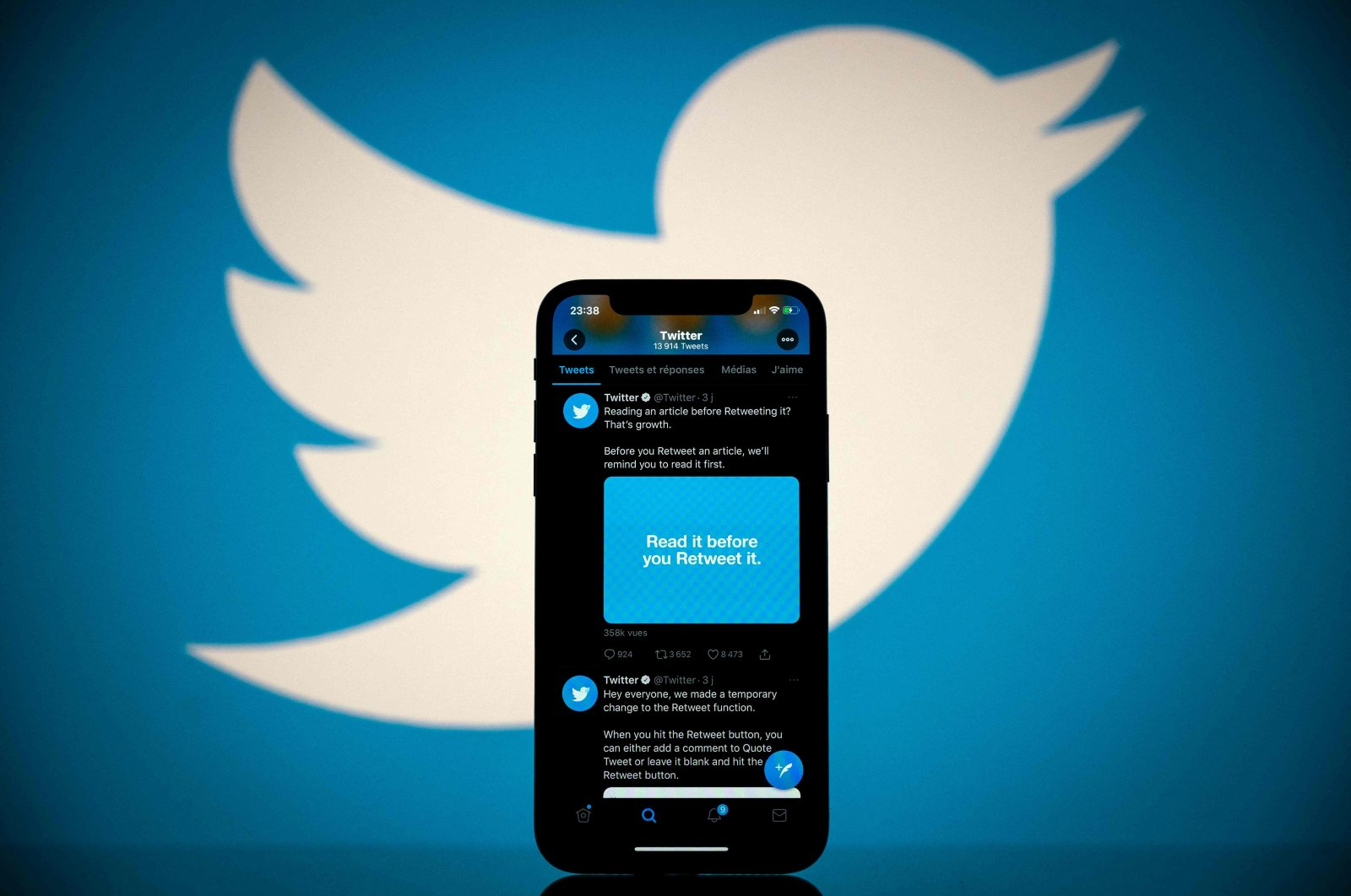 The logo of social media platform Twitter is displayed behind a smartphone with Twitter's application visible on the screen, Toulouse, France, Oct. 26, 2020. (AFP Photo)