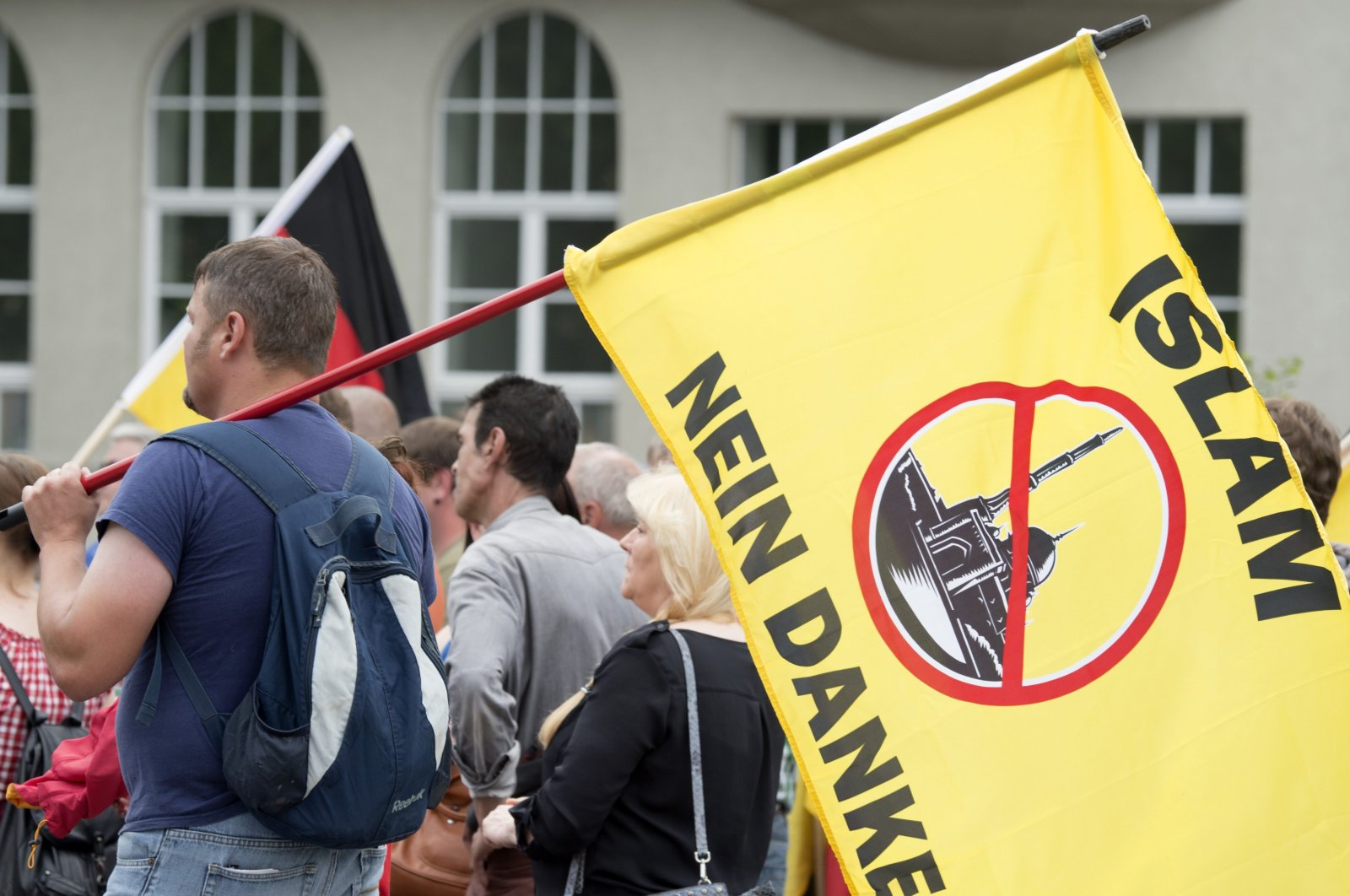 """A supporter of the right-wing group """"Patriotic Europeans say no"""" holds a flag reading """"Islam, no thanks"""" during a rally in Erfurt, Germany, June 4, 2016. (AP Photo)"""