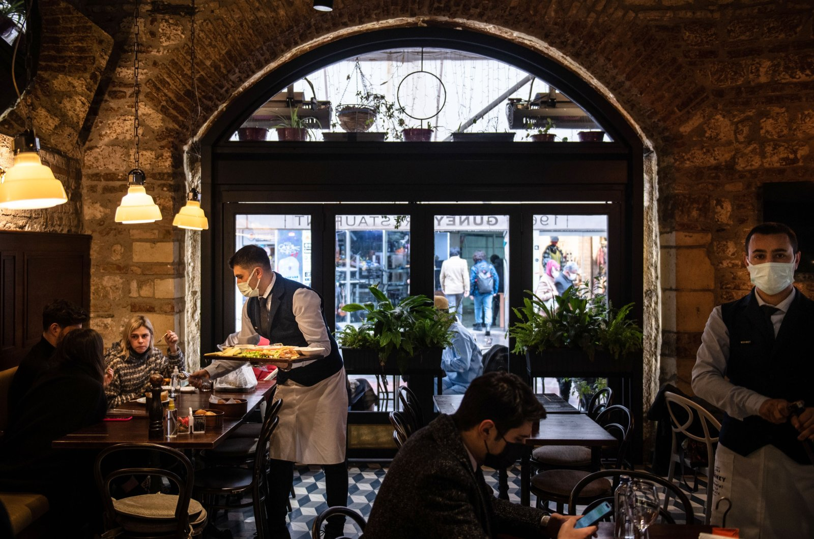 A waiter wearing face mask serves to the customers having lunch at a re-opened restaurant in the Galata district in Istanbul, Turkey, March 02, 2021. (Getty Images)