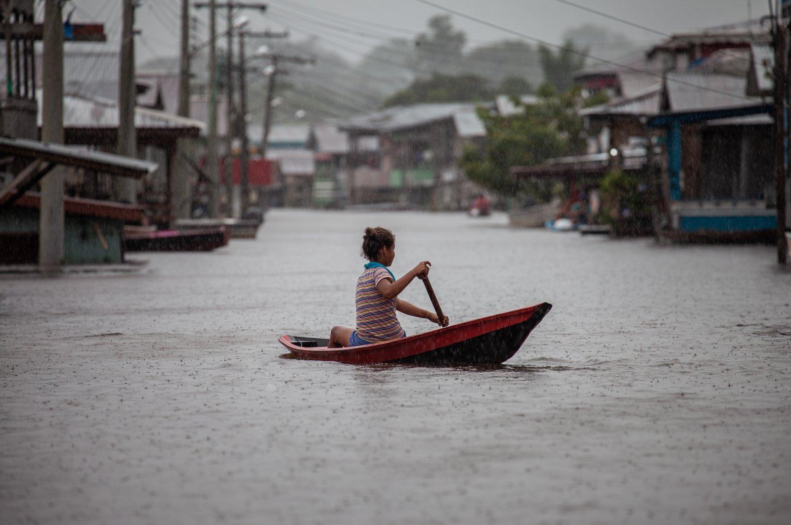 A girl paddles a small canoe through flooded streets n Anama, Amazonas, Brazil, May 23, 2021. (EPA Photo)