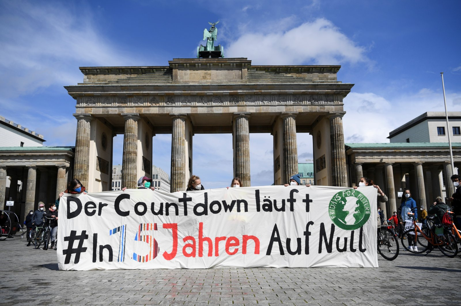 """Cyclists attend a Fridays for Future bike protest for climate neutrality till 2035, in front of the Brandenburg Gate in Berlin, Germany May 7, 2021. The banner reads: """"The countdown is running! In 15 years to zero."""" (Reuters File Photo)"""