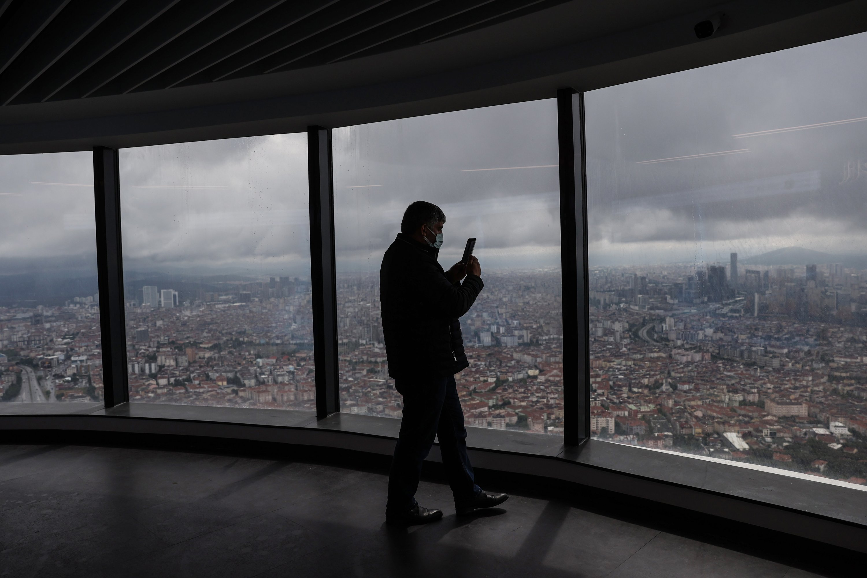 A visitor takes a photo at an observation deck at the Çamlıca Tower in Üsküdar, Istanbul, Turkey, June 1, 2021.