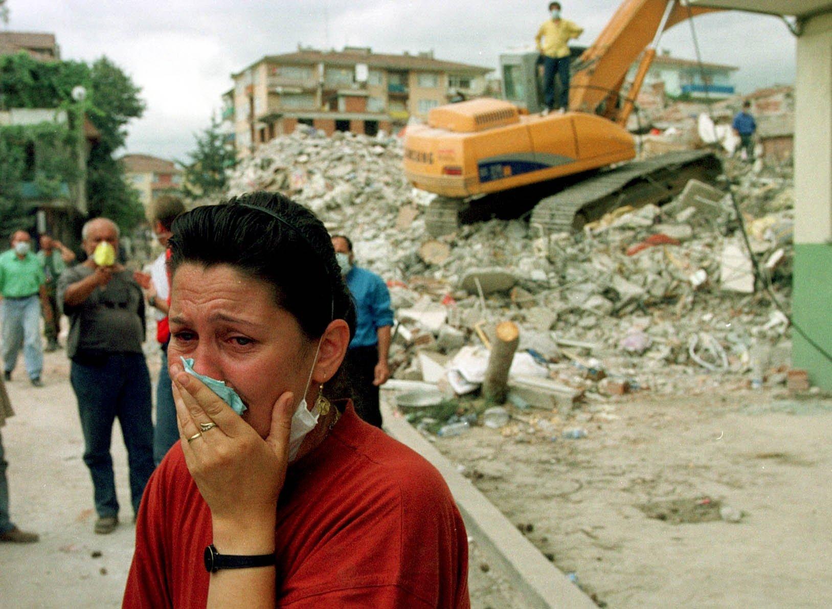 23 Ağustos 1999'da Türkiye'nin Golgotha kentindeki enkazdan tahliye edildikten sonra 16 yaşındaki erkek kardeşinin kalıntıları ambulansla kurtarma görevlileri tarafından taşınırken bir kadın ağlıyor.  (AP fotoğrafı)