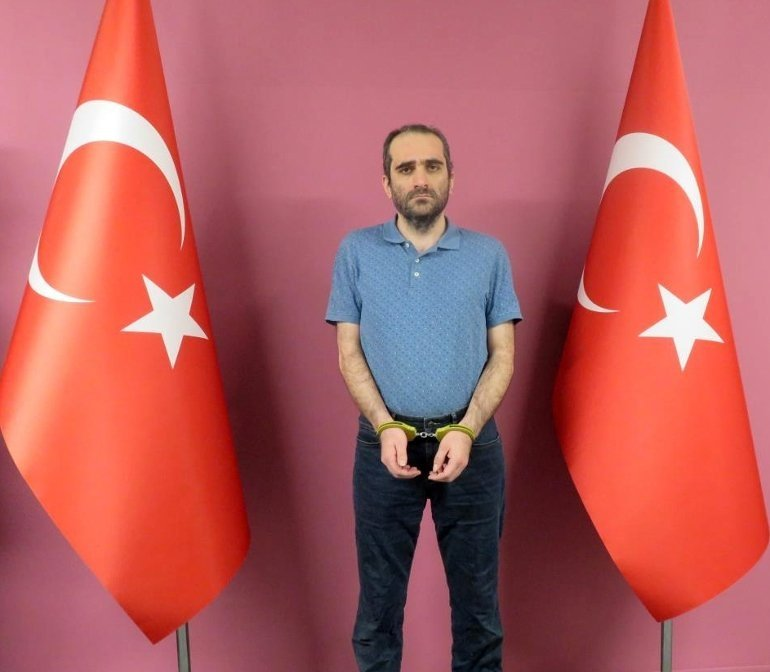 In this photo provided by the National Intelligence Organization (MIT), Selahaddin Gülen stands in handcuffs between two Turkish flags at an undisclosed location, on an unknown date. (AA Photo/via MIT)