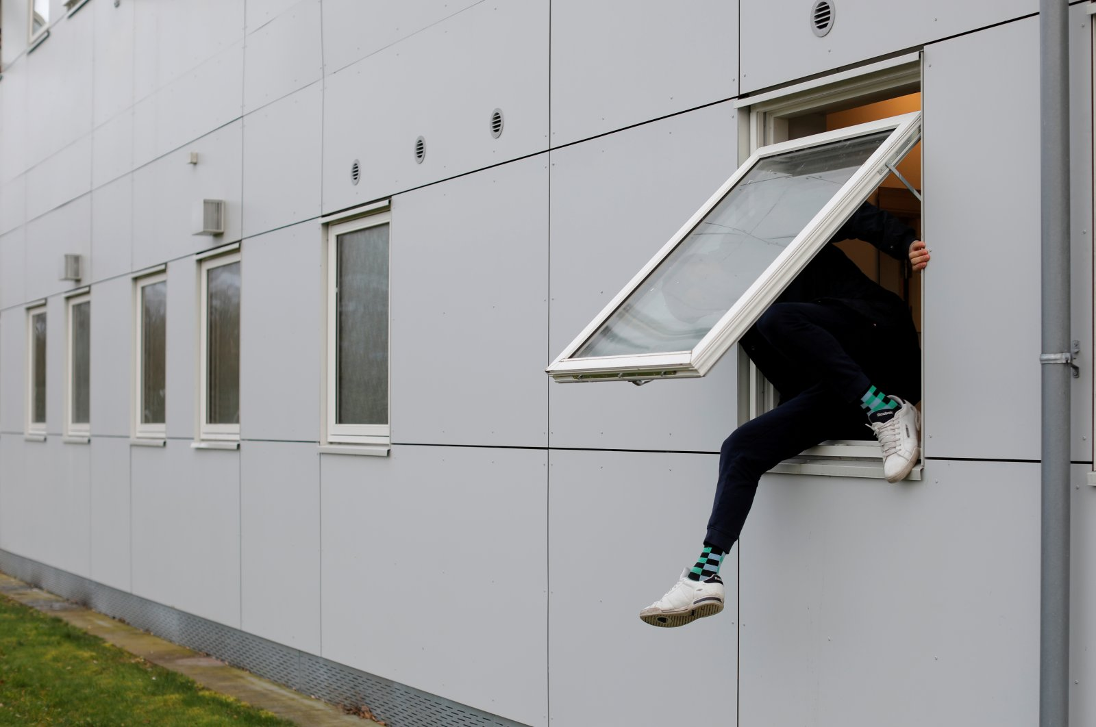 A resident climbs through a window at Kaershovedgaard, a former prison and now a departure center for rejected asylum seekers in Jutland, Denmark, March 26, 2019. (Reuters Photo)