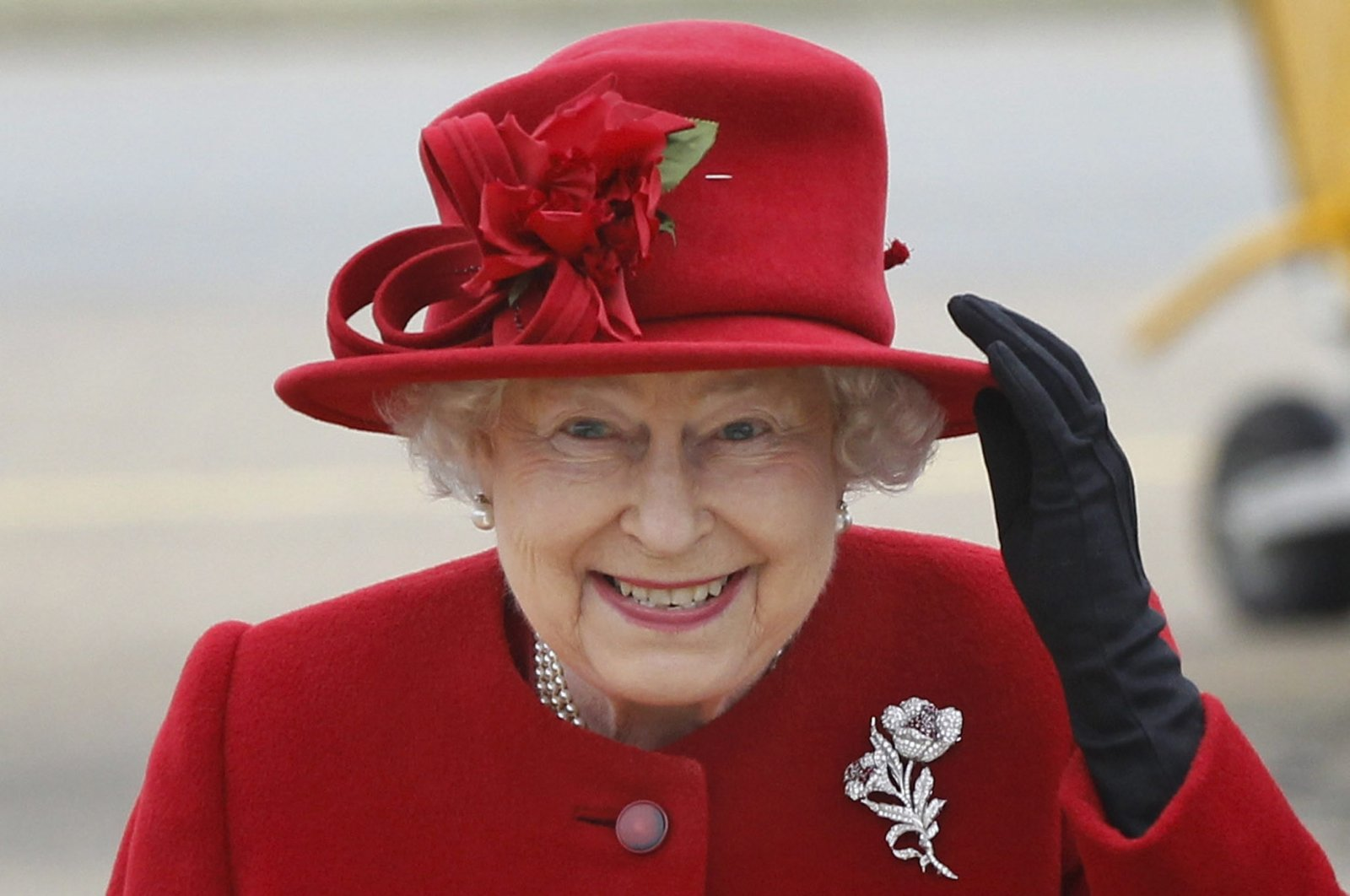 Queen Elizabeth II holds on to her hat in high winds during a visit to RAF Valley where Prince William is stationed as a search and rescue helicopter pilot in Holyhead, United Kingdom, April 1, 2011. (Getty Images)