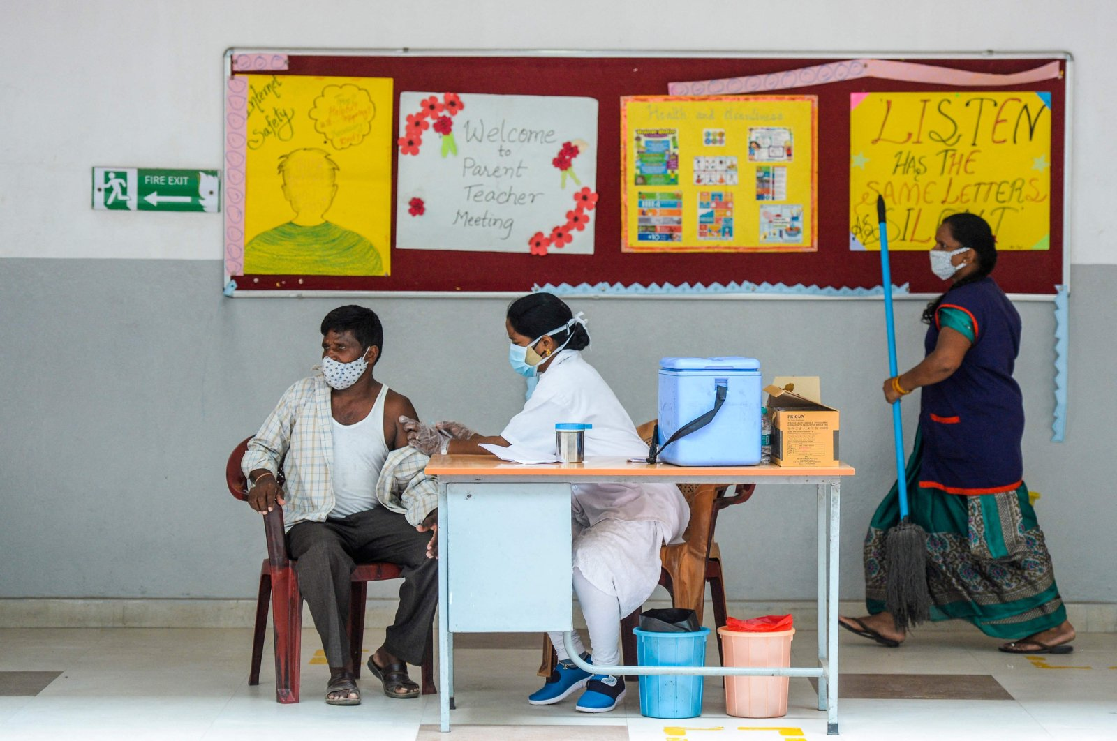 A health worker inoculates a man with a dose of the Covishield Covid-19 coronavirus vaccine during a vaccination drive for auto-rickshaw and taxi drivers at a school in Hyderabad, India, June 4, 2021. (AFP Photo)