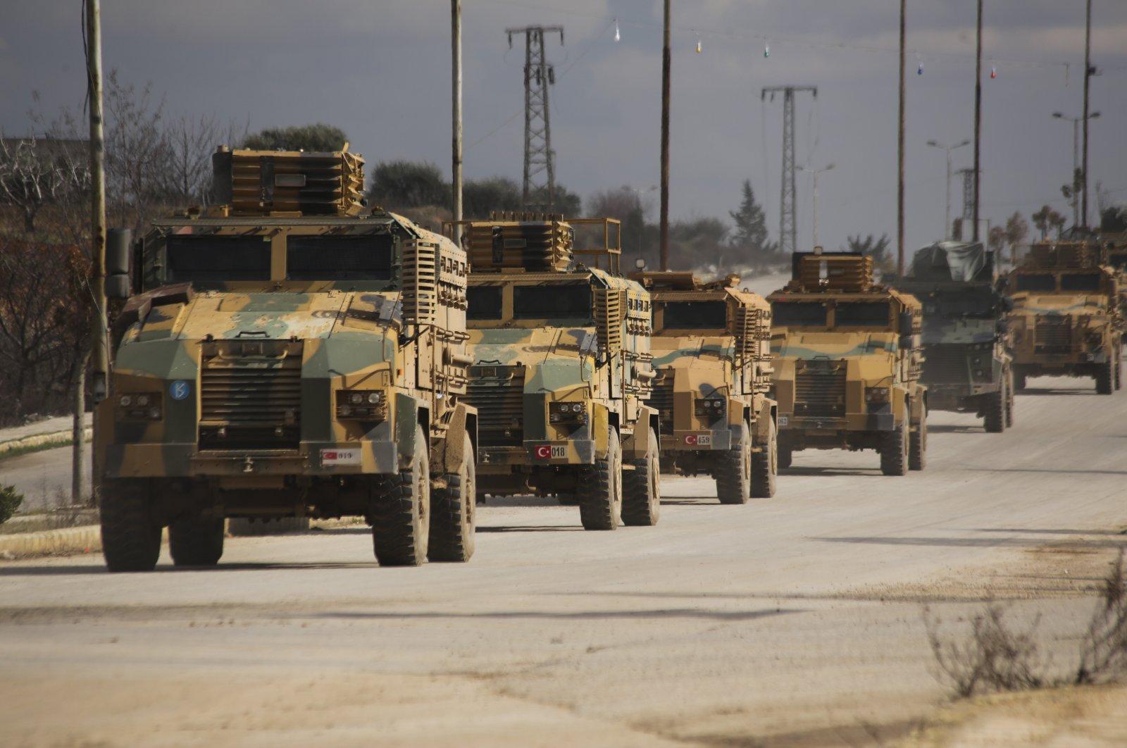 Turkish military convoy drives in Idlib province, Syria, Feb. 22, 2020. (AP Photo)