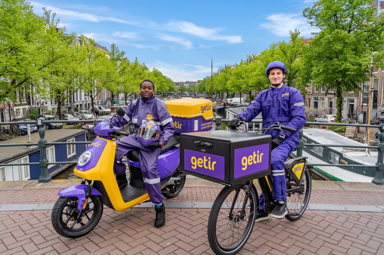 Getir couriers pose in front of a canal in Amsterdam, The Netherlands, May 28, 2021. (Courtesy of Getir)