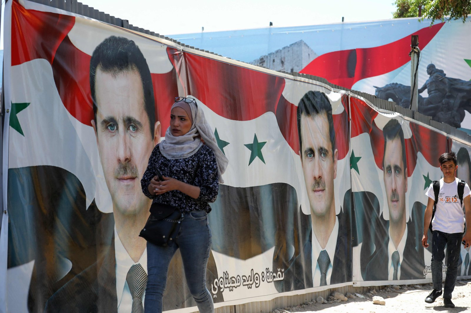 People walk past election campaign billboards depicting Bashar al-Assad, in the capital Damascus, Syria, on May 25, 2021. (AFP Photo)