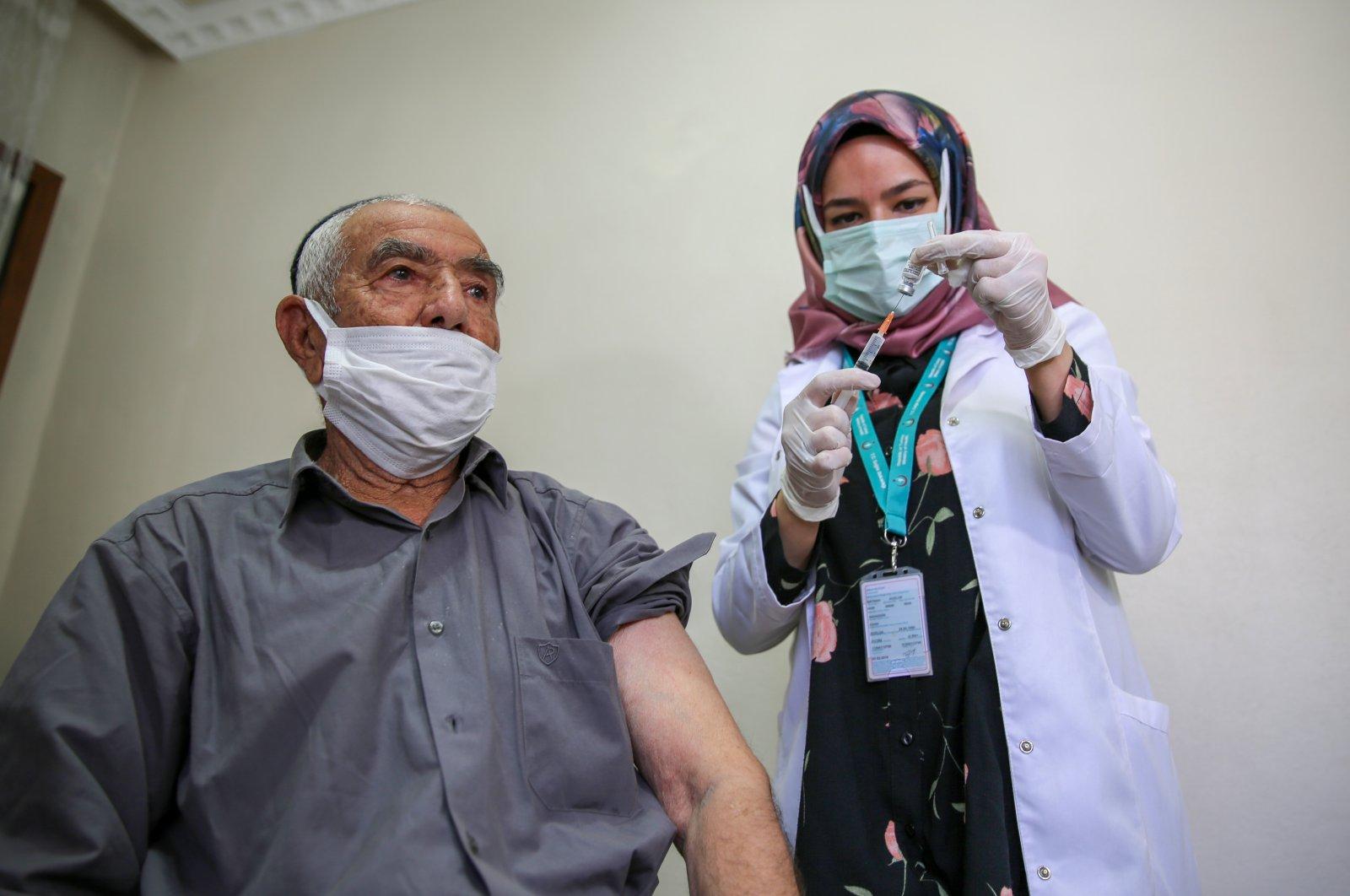 A health care worker readies a COVID-19 jab for 90-year-old Ahmet Gündoğdu, in Diyarbakır, southeastern Turkey, June 3, 2021. (AA PHOTO)
