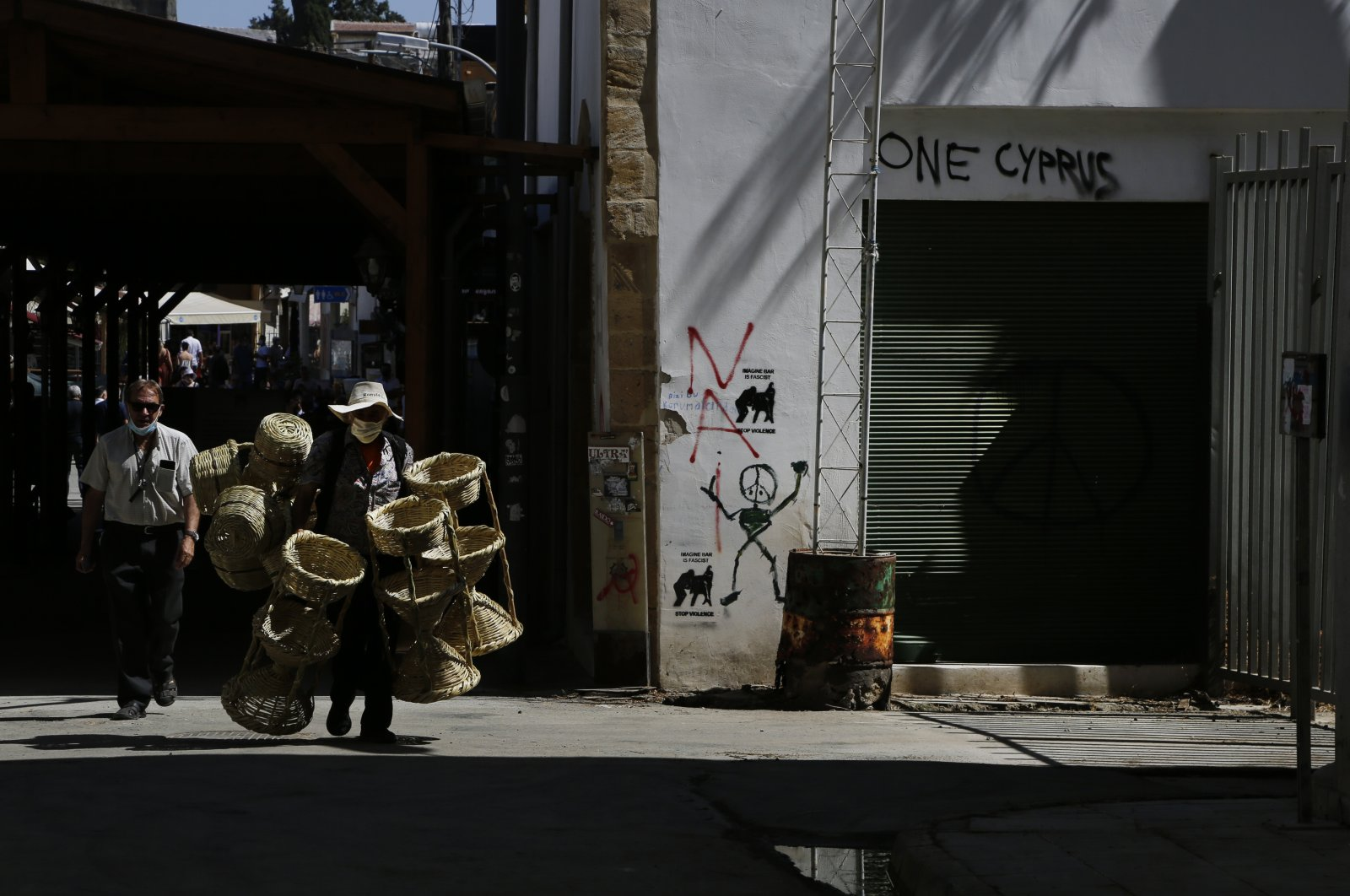 An elderly Turkish Cypriot man, wearing a protective face mask, carries his baskets for sale as he crosses from the Turkish north to the Greek south at the Ledra checkpoint in divided capital Nicosia, the island of Cyprus, June 4, 2021. (AP Photo)