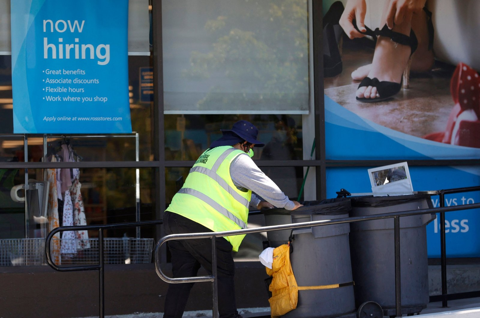 A worker pushes a cart by a 'Now Hiring' sign outside of a store in Sausalito, California, U.S., June 3, 2021. (AFP Photo)