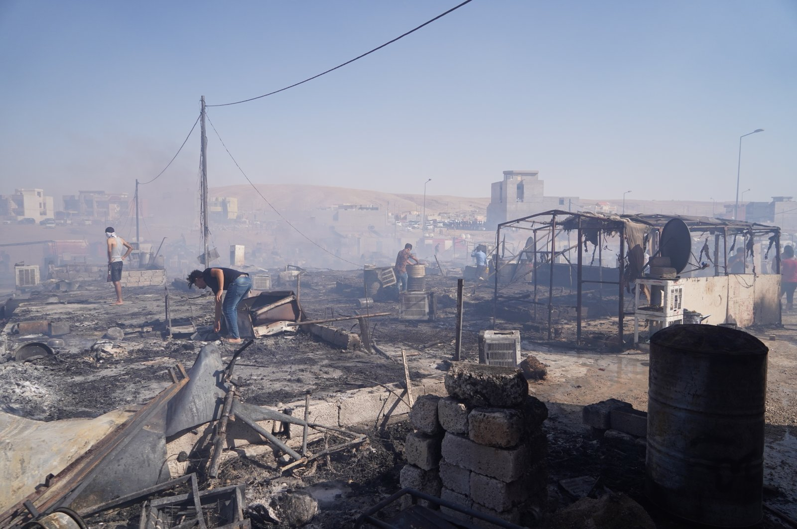 Survivors sift through the remains of tents destroyed during a massive blaze that swept through the Yazidi refugee camp in Duhok, Iraq, June 4, 2021. (AA Photo)