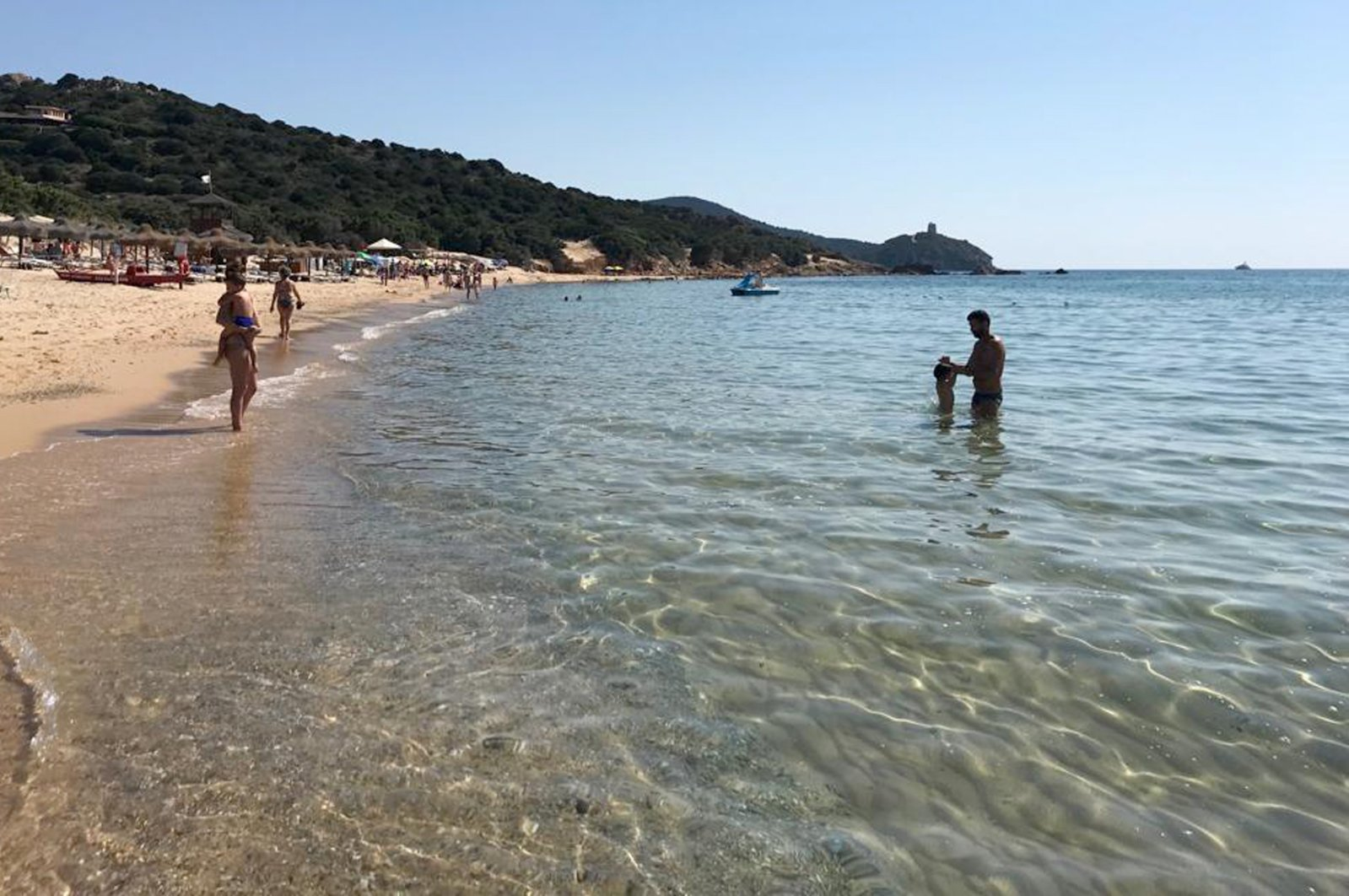 People enjoy the white sand and pristine waters of Chia beach, on the Italian island of Sardinia, Italy, June 29, 2019. (AP Photo)