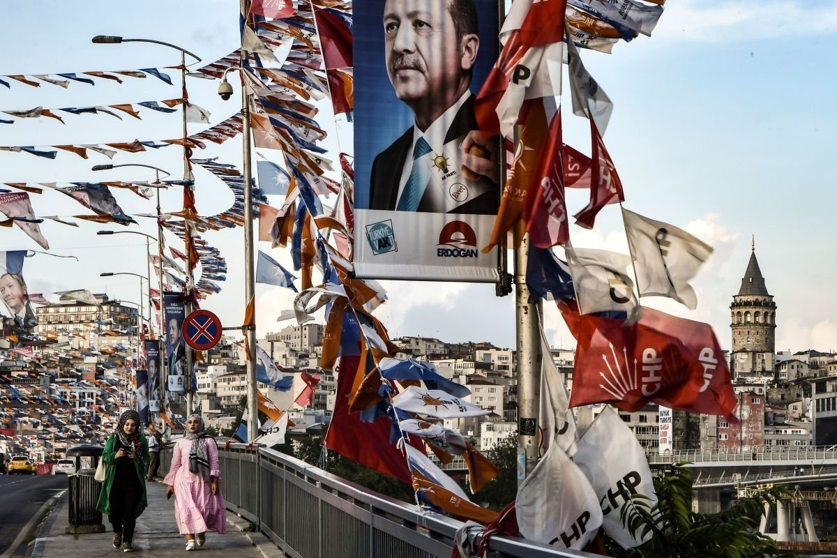 Women walk on a bridge past campaign banners ahead of the June 24 presidential and parliamentary elections in Istanbul, Turkey, June 18, 2018.