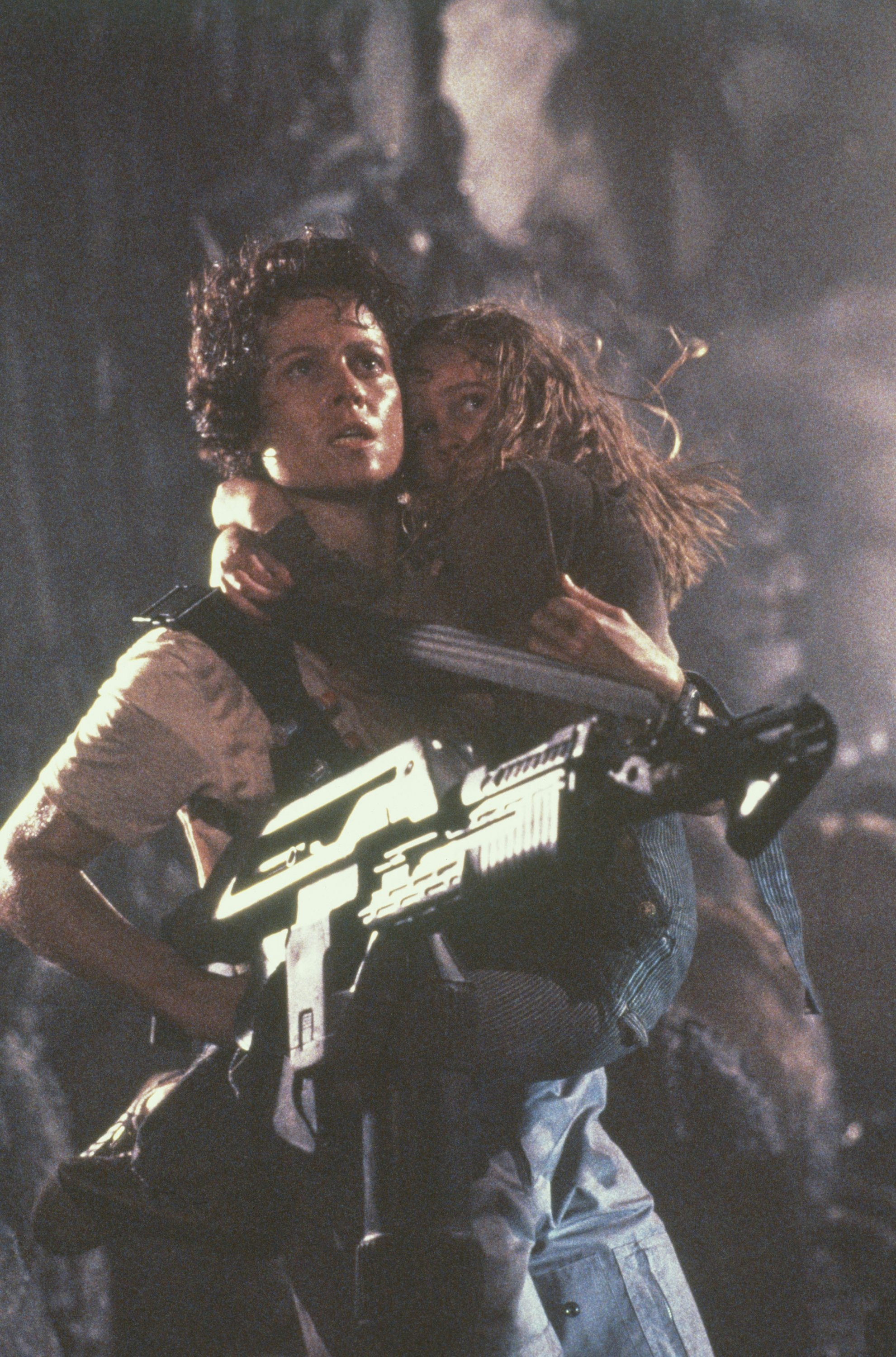American actresses Sigourney Weaver carries Carrie Henn on the set of the film 'Aliens', directed by James Cameron and released in 1986. (Getty Images)