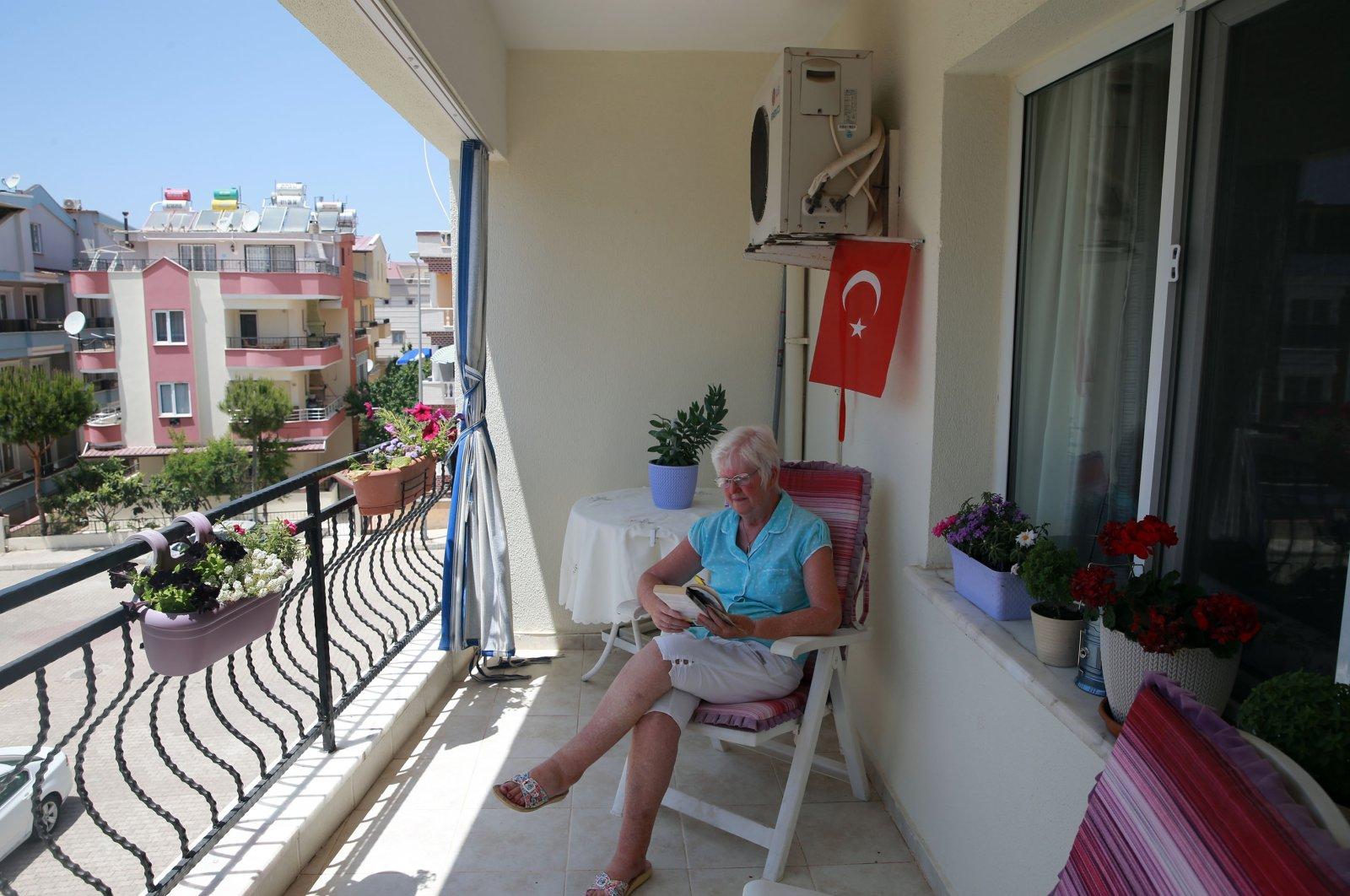 British expat Helene McGowan reads a book on her house's balcony, in Didim, Aydın, western Turkey, June 6, 2021. (AA PHOTO)