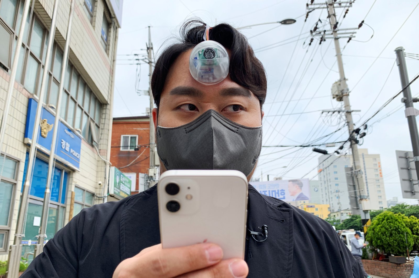 """South Korean industrial designer Paeng Min-wook showcases a robotic eye, called """"The Third Eye,"""" on his forehead as he uses his mobile phone while walking on the street, in Seoul, South Korea, March 31, 2021. (Reuters Photo)"""