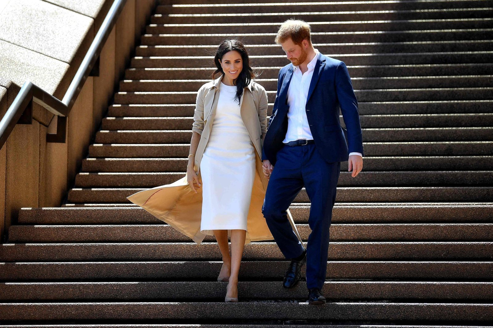 Britain's Prince Harry and his wife Meghan walk down the stairs of the iconic Opera House in Sydney to meet people, Oct. 16, 2018. (AFP File Photo)