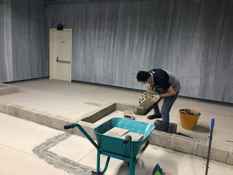 "A man puts down a concrete brick as part of an art installation at SALT Galata's ""Scratch and Surface"" exhibition, Istanbul, Turkey. (Photo by Matt Hanson)"