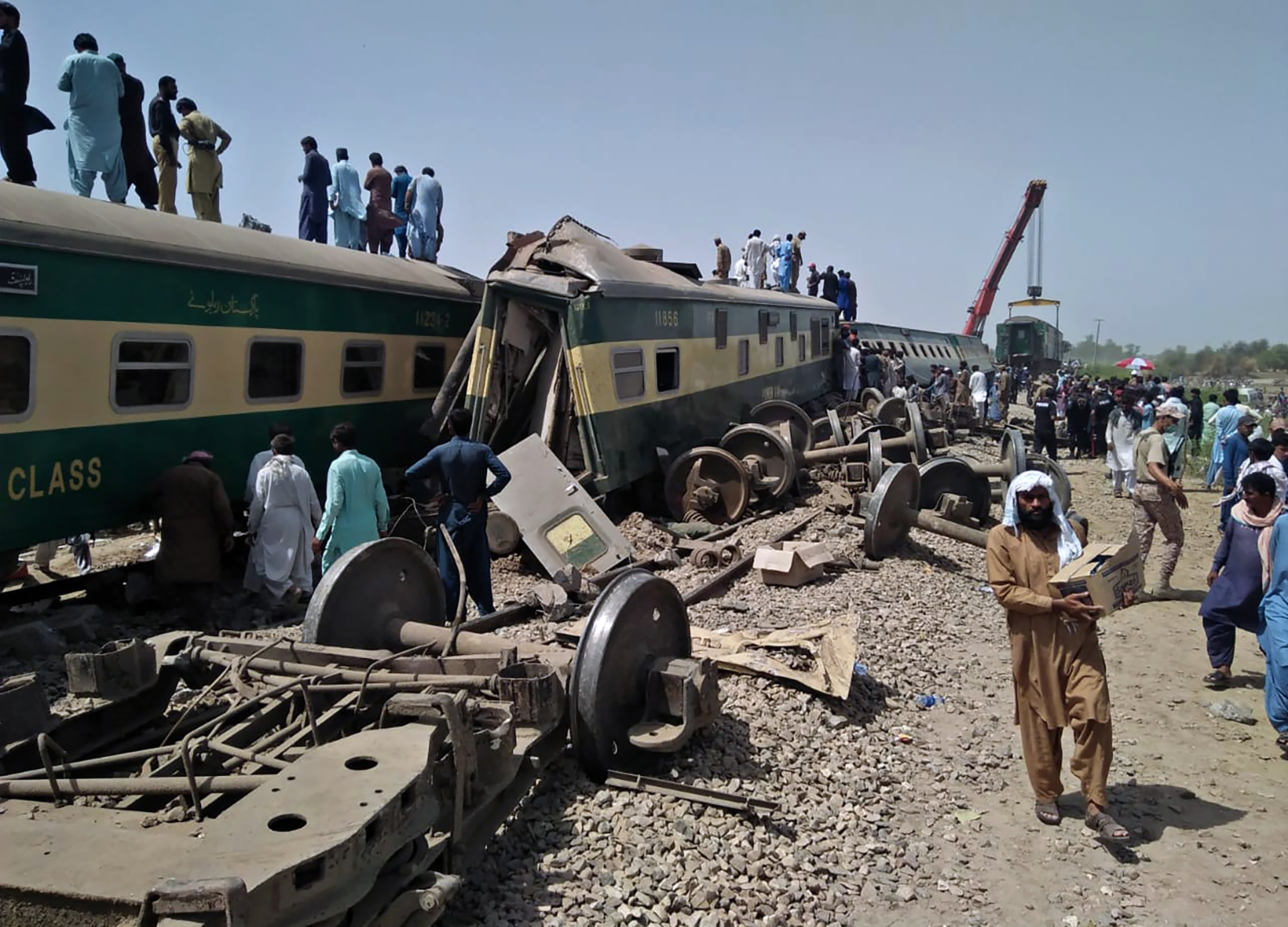 Soldiers and volunteers work at the site of a train collision in Ghotki district in southern Pakistan, Monday, June 7, 2021. (AP Photo)