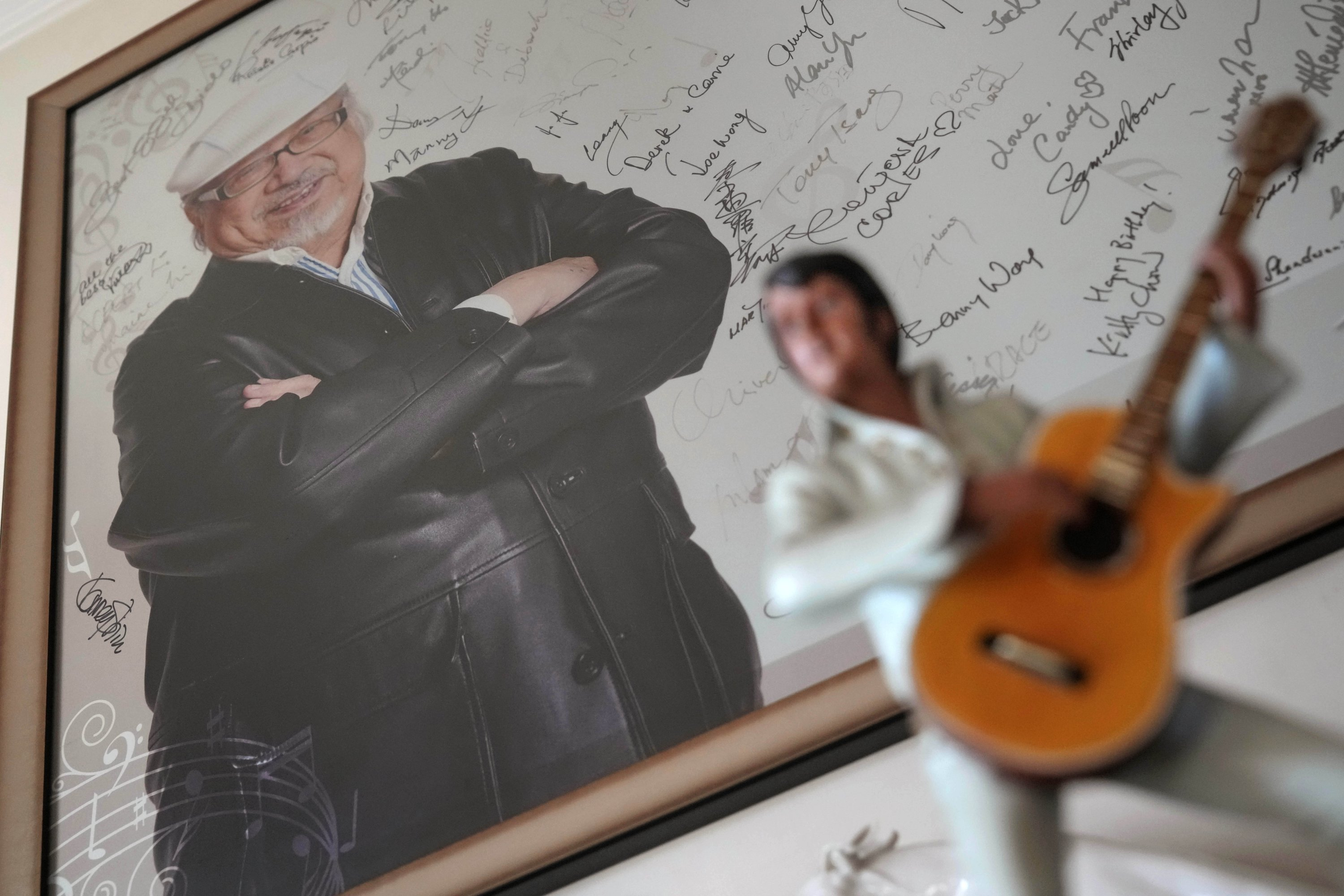 A poster featuring a portrait of Hong Kong's oldest DJ Ray Cordeiro is displayed at his home in Hong Kong, May 27, 2021. (AP Photo)