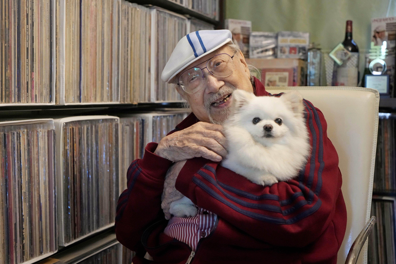 Ray Cordeiro, Hong Kong's oldest DJ, holds his dog at home in Hong Kong, May 27, 2021. (AP Photo)