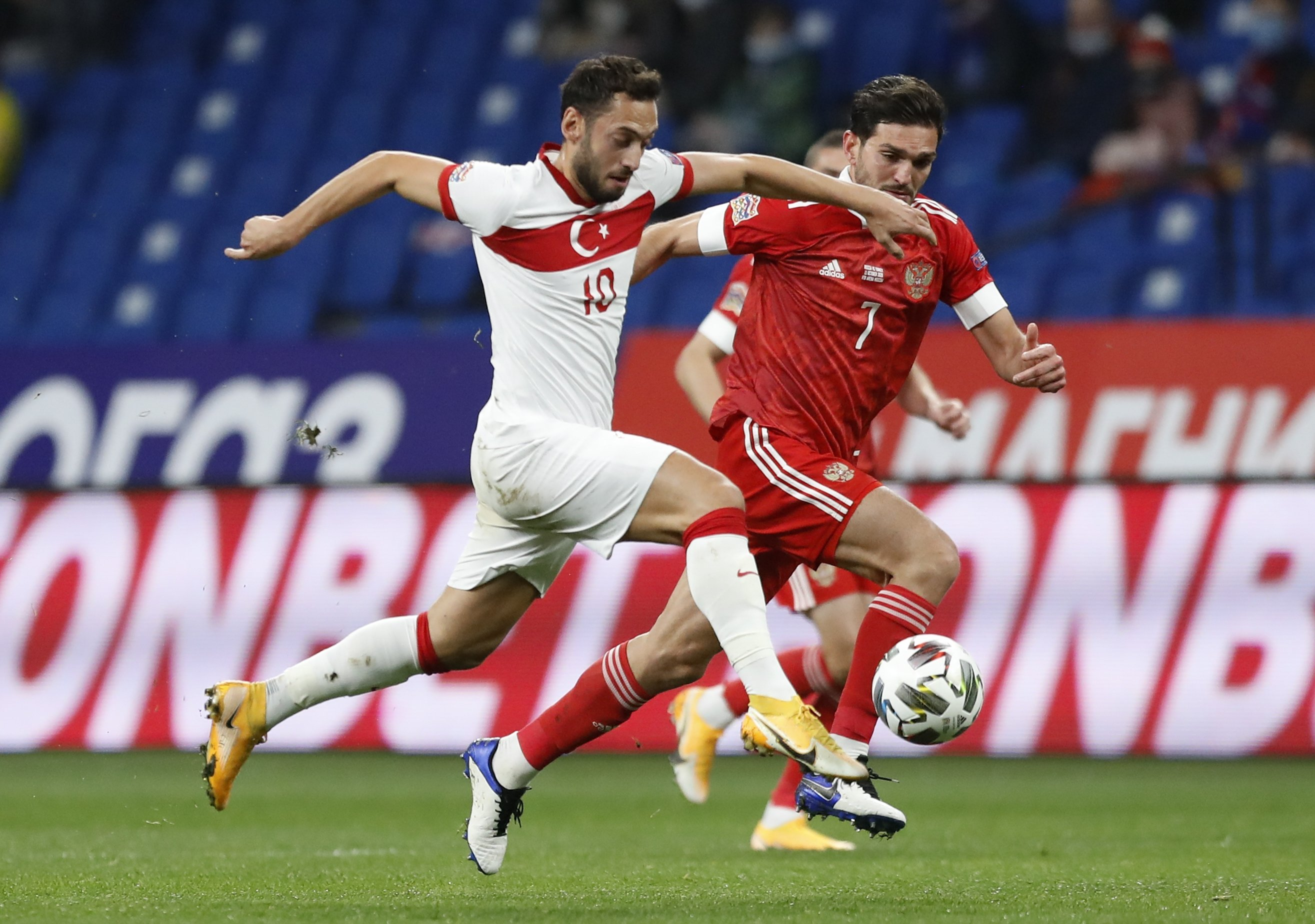 Turkey's Hakan Çalhanoğlu (L) plays the ball past Russia's Magomed Ozdoyev during a UEFA Nations League match at Dinamo Stadium, Moscow, Russia, Oct. 11, 2020. (AP Photo)