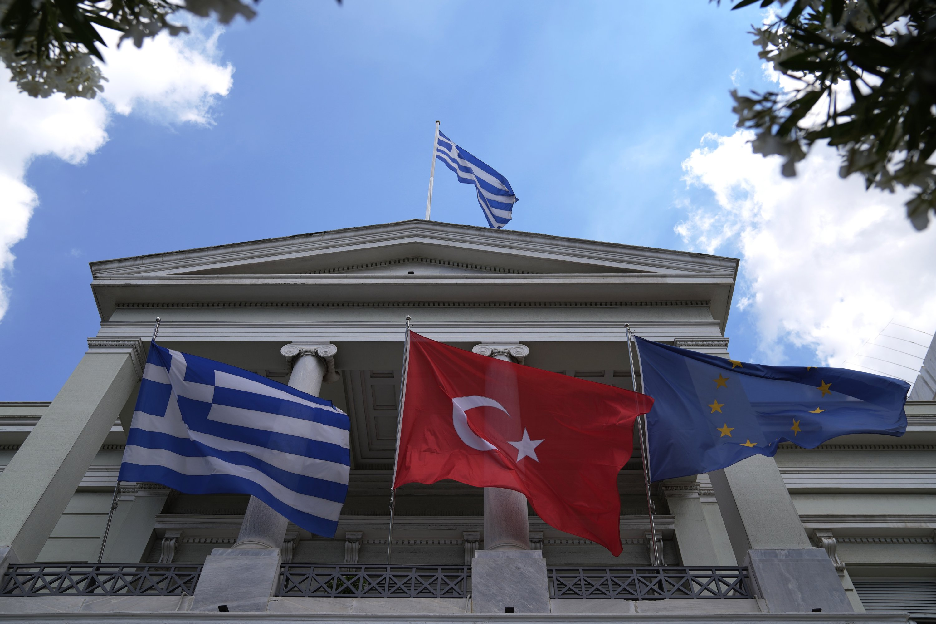 From left to right, Greek, Turkish and EU flags wave on the Greek Foreign Ministry building before a meeting between Foreign Minister Mevlüt Çavuşoğlu and Greek Foreign Minister Nikos Dendias, Athens, Greece, May 31, 2021. (AP Photo)