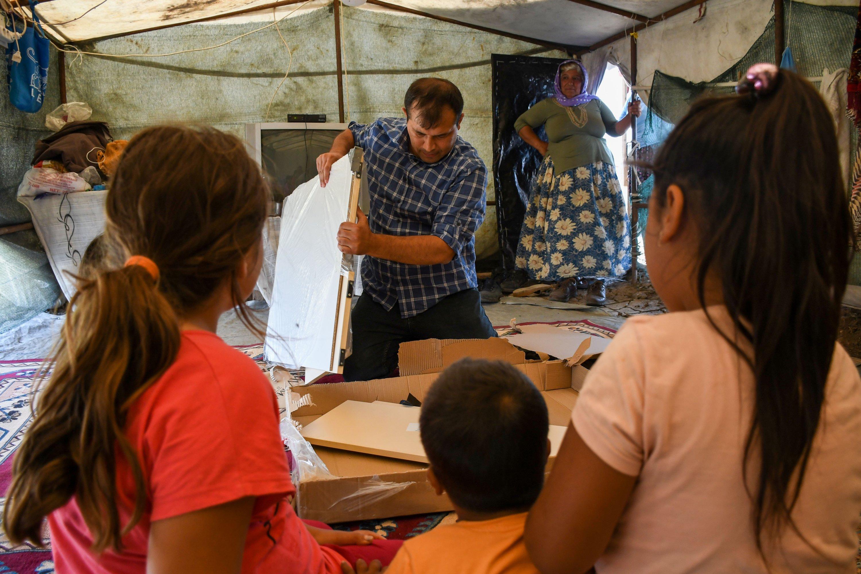 Ahmet Yerlikaya installs a bookshelf for children, in Adana, southern Turkey, June 6, 2021. (AA PHOTO)
