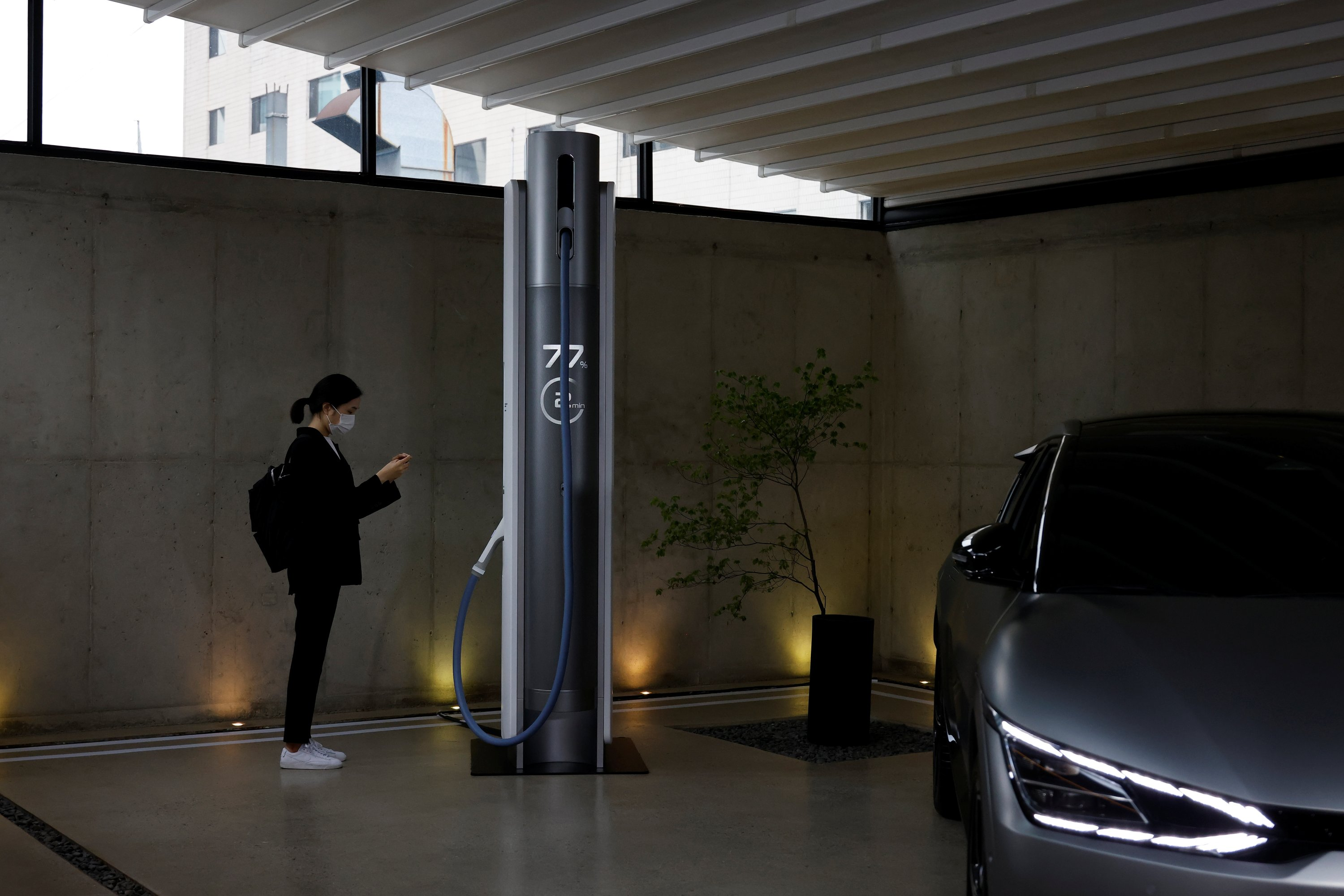A journalist takes photographs of an Ultra Fast EV Charger next to a Kia EV6 GT during a photo opportunity in Seoul, South Korea, June 1, 2021. (Reuters Photo)