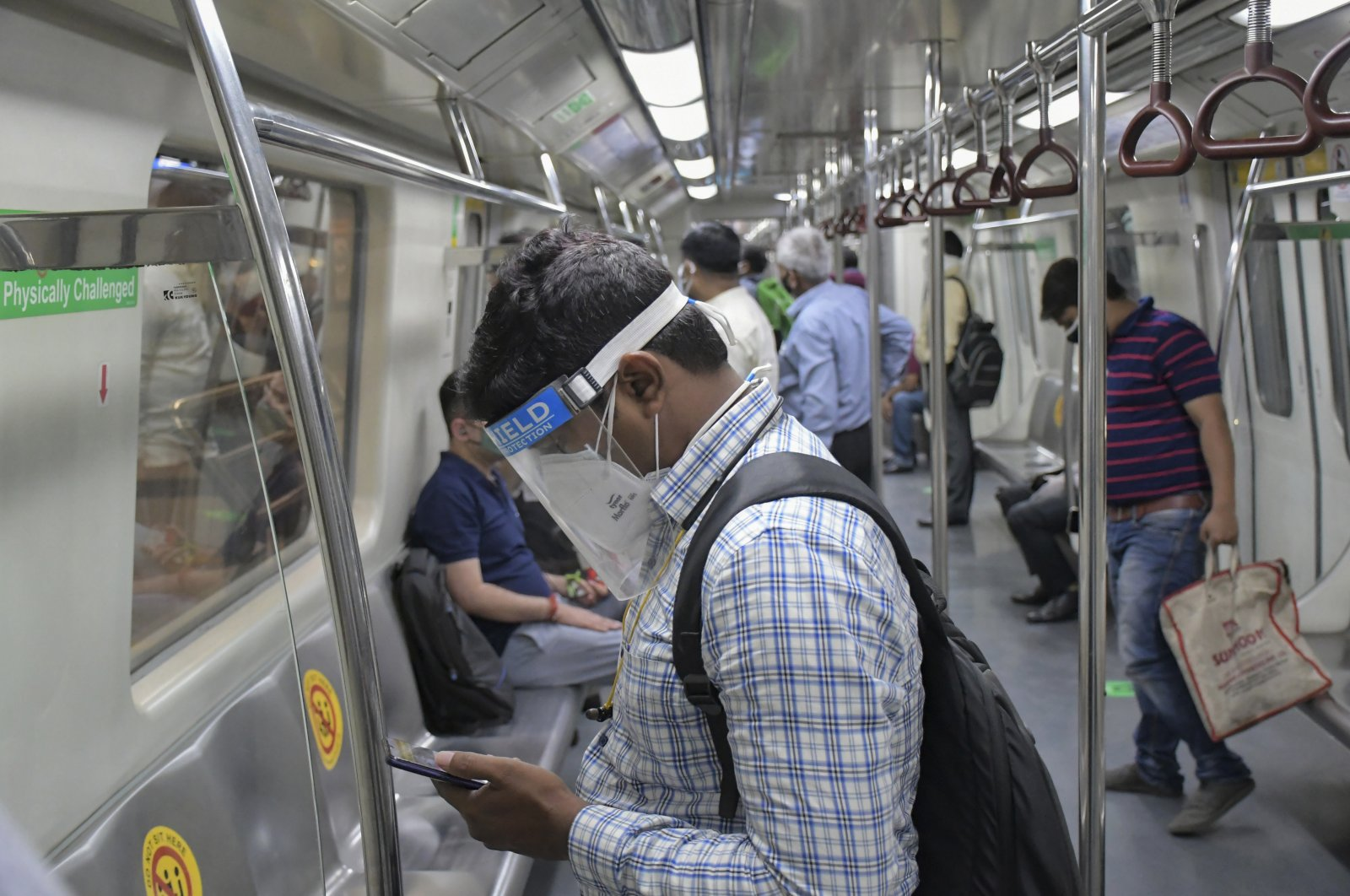 Commuters use the Delhi Metro, which serves the Indian capital and adjoining areas, as it resumed operations at 50% capacity, New Delhi, India, Monday, June 7, 2021. (AP Photo)