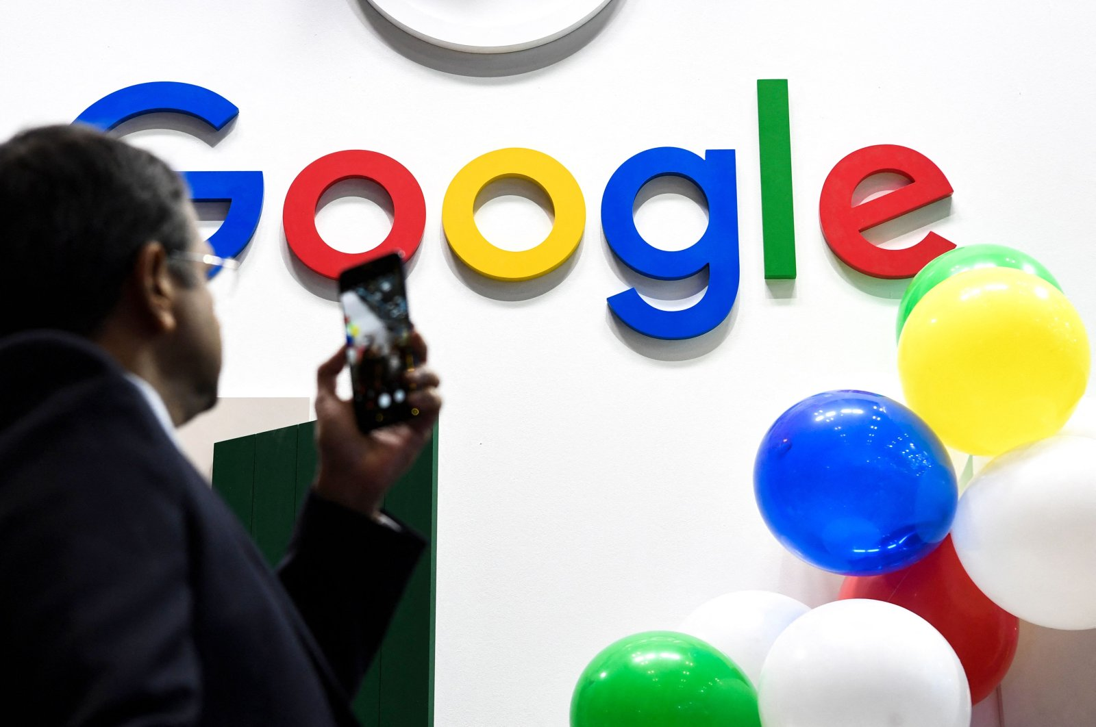 A man takes a picture with his mobile phone of the logo of the U.S. multinational technology and internet-related services company Google as he visits the Vivatech startups and innovation fair, Paris, France, May 16, 2019. (AFP File Photo)