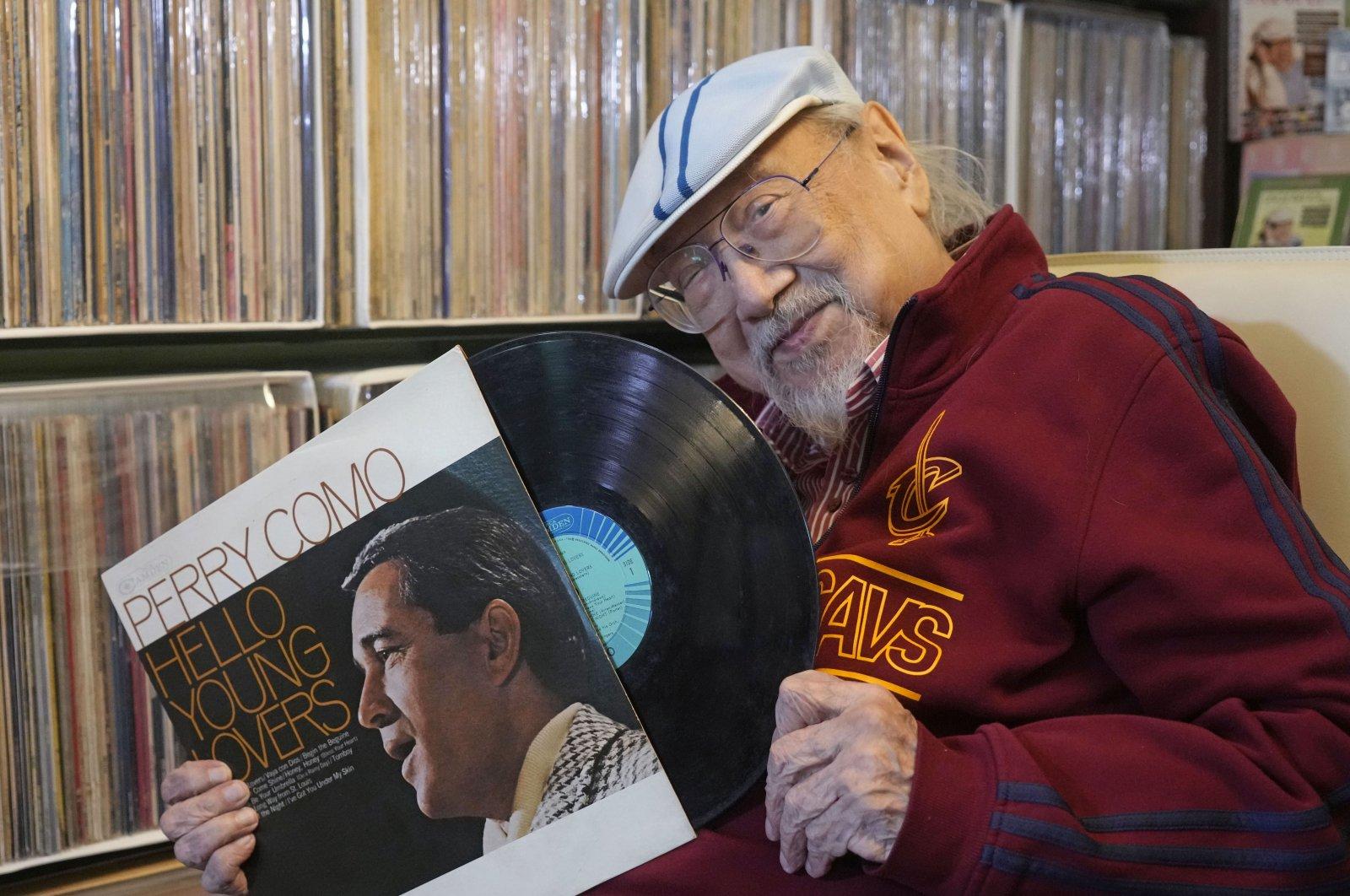 Ray Cordeiro, Hong Kong's oldest DJ shows a vinyl record at his home in Hong Kong, May 27, 2021. (AP Photo)