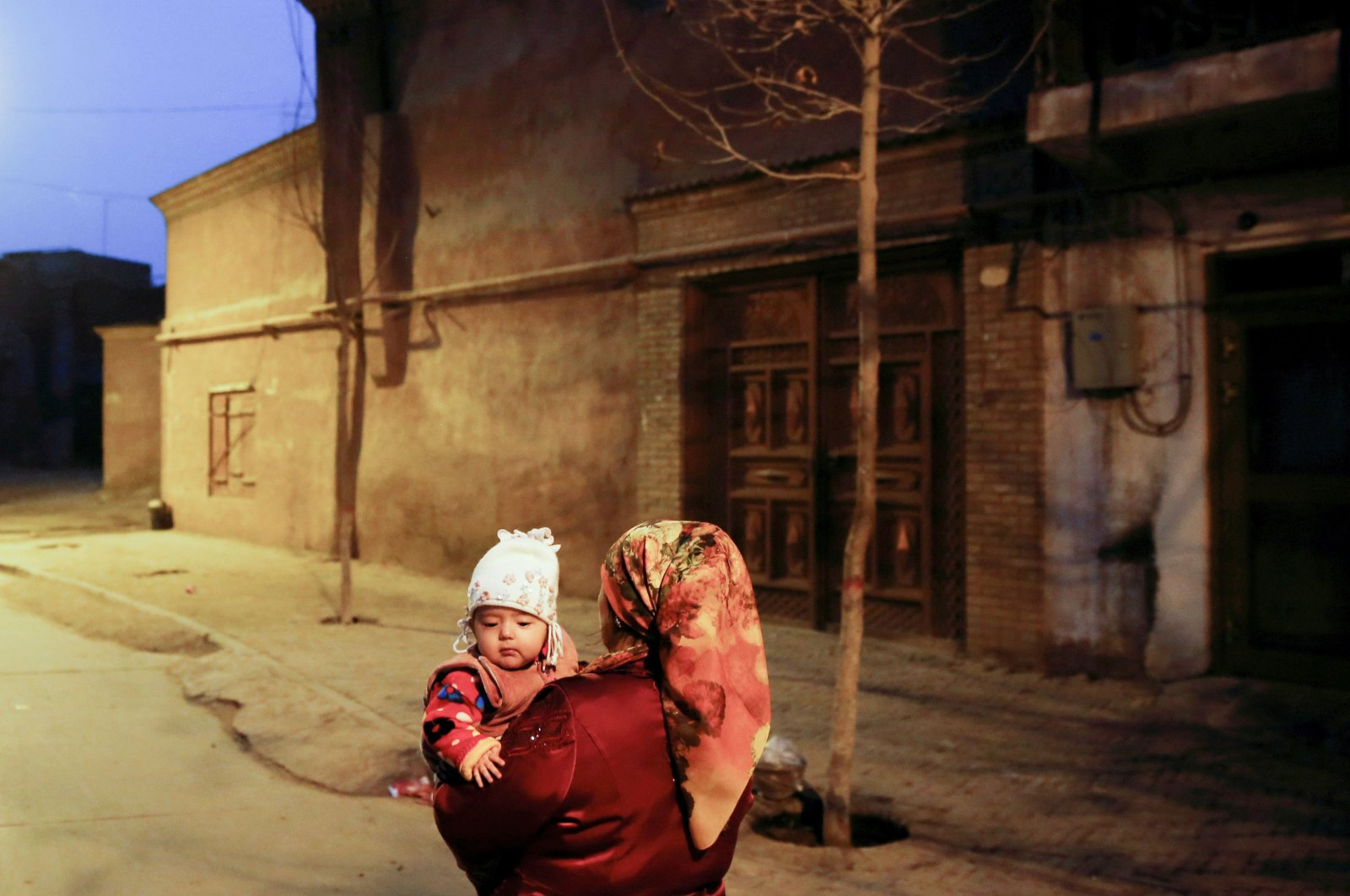 A woman carries a child at night in the old town of Kashgar, Xinjiang Uighur Autonomous Region, China, March 23, 2017. (Reuters Photo)