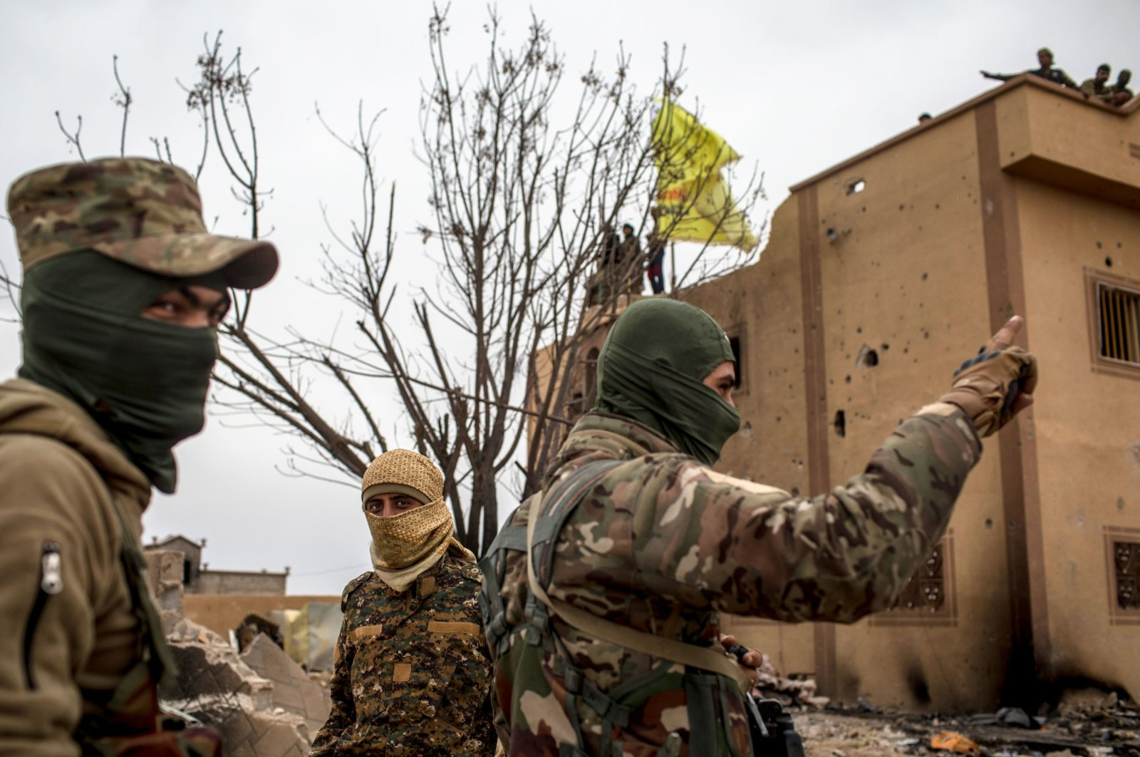 YPG/PKK fighters are seen in front of a building at a position on March 24, 2019, in Baghouz, Syria. (Getty Images)