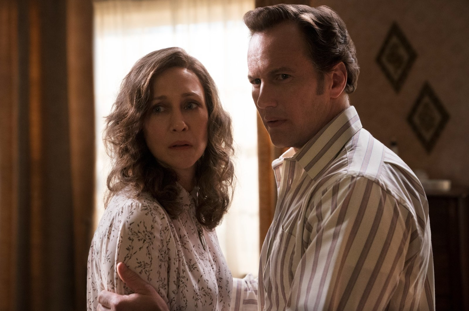 """Vera Farmiga (L), and Patrick Wilson stand next to each other, in a scene from """"The Conjuring: The Devil Made Me Do It."""" (Warner Bros. via AP)"""