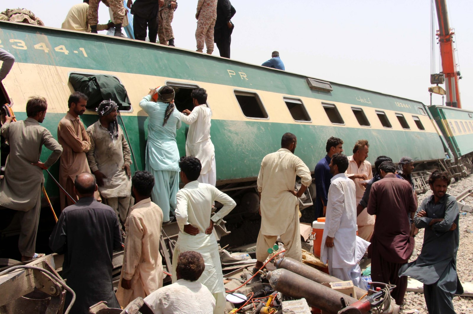 Rescue workers assess the scene following a train accident in Dharki, Sindh province, Pakistan, June 7, 2021. (EPA Photo)
