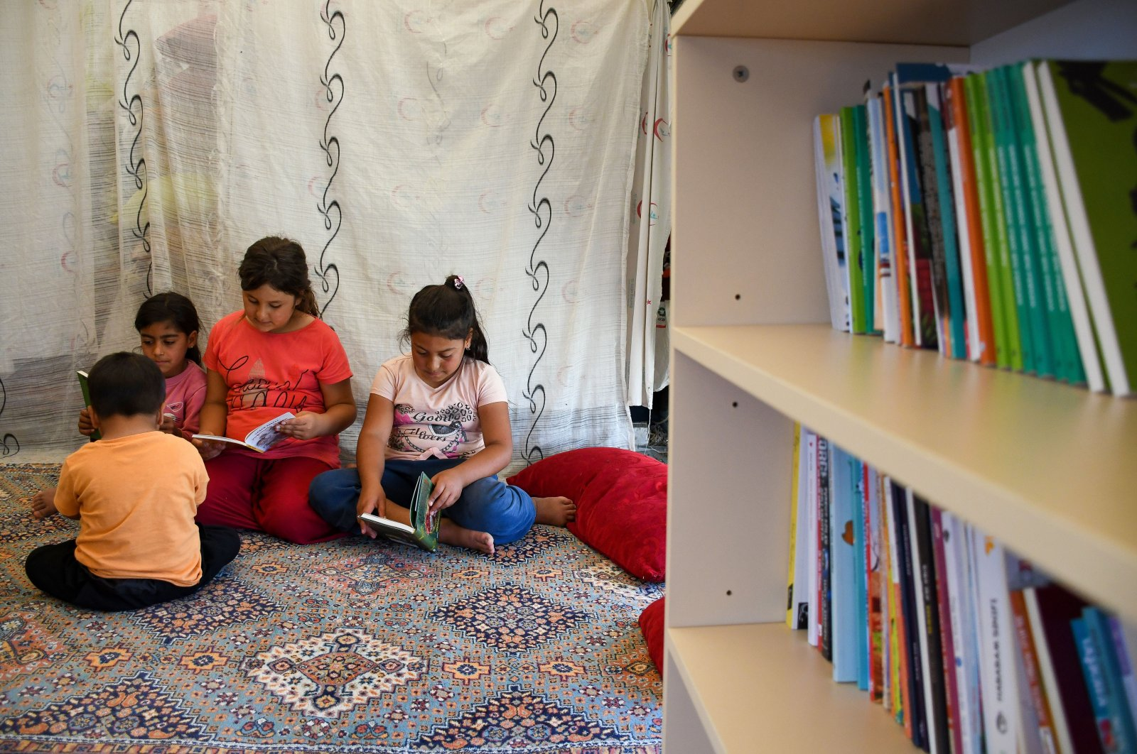 Children read books inside a tent, in Adana, southern Turkey, June 6, 2021. (AA PHOTO)