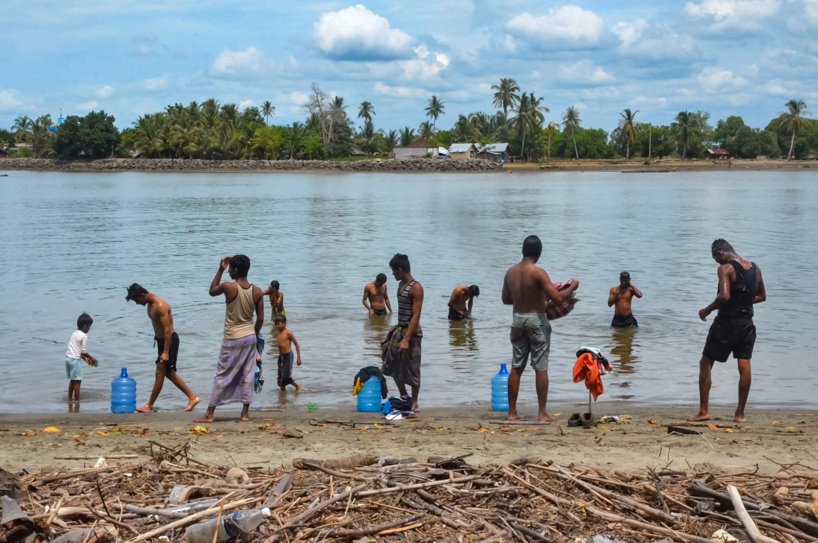 Rohingya refugees bathe at a beach in Pulau Idaman, a small island off the coast of East Aceh in northern Sumatra on June 5, 2021, a day after about 80 Rohingya landed their vessel off the Indonesian coast. (AFP Photo)
